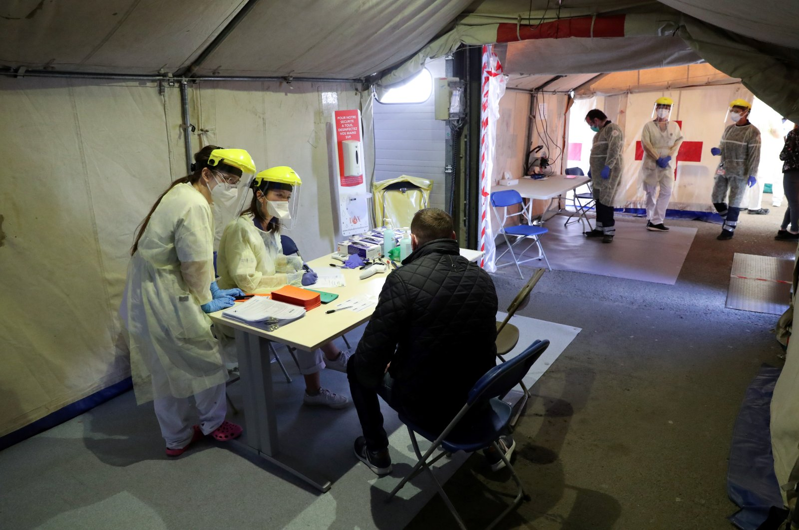 Members of medical personnel prepare before testing a person for the coronavirus disease (COVID-19) at the testing site of the Erasme Hospital in Brussels, Belgium, Monday, March 30, 2020.  (Reuters Photo)