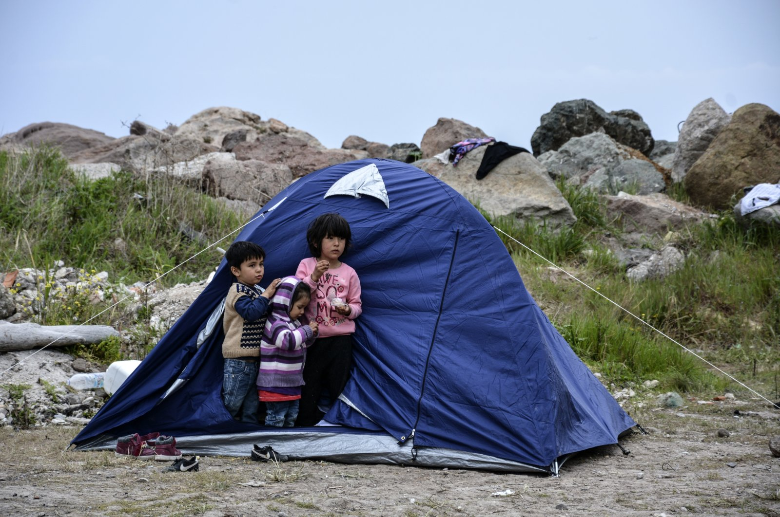 Children stand outside a tent in the village of Petra on the northeastern Aegean island of Lesbos, Greece, Friday, March 27, 2020. (AP Photo)