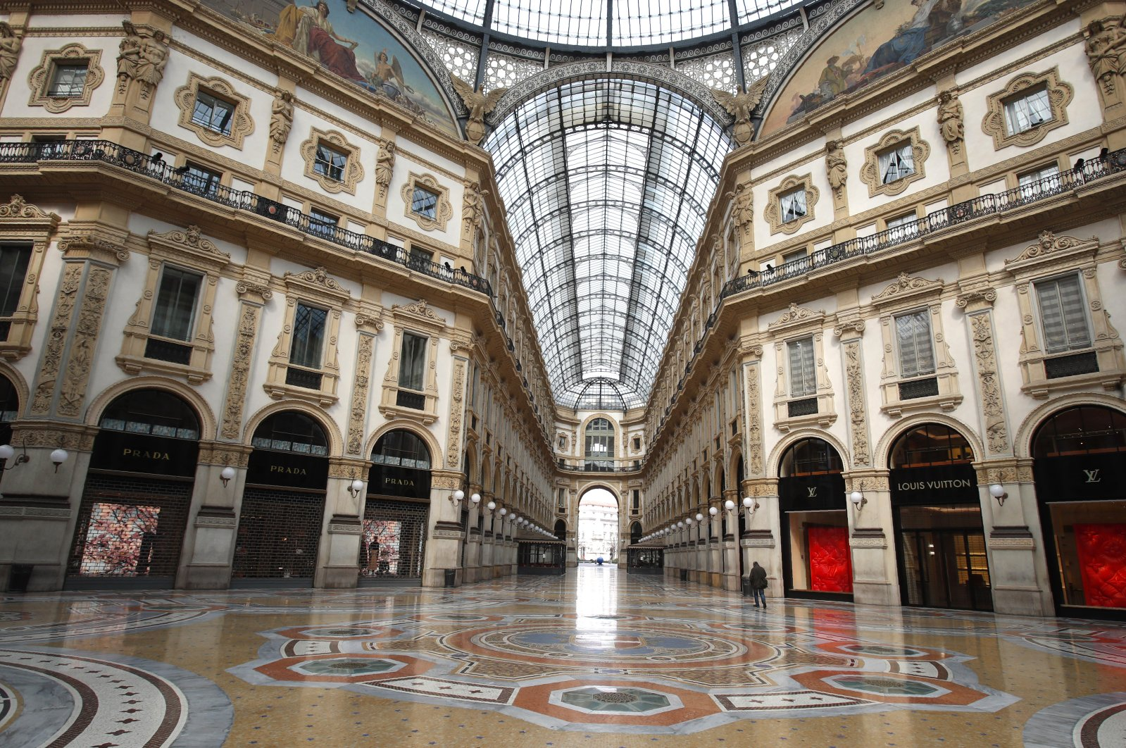 In this photo, a man walks in an empty Vittorio Emanuele II gallery shopping arcade, in downtown Milan, Italy, Sunday, March 22, 2020. (AP Photo)