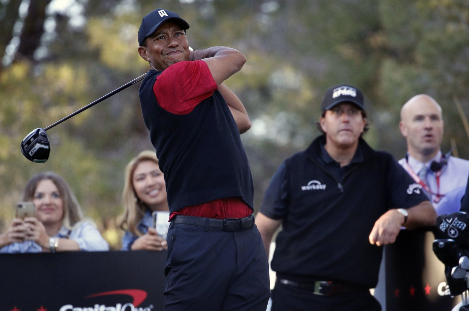 Tiger Woods tees off as Phil Mickelson watches at Shadow Creek golf course, Las Vegas, Nov. 23, 2018. (AP Photo)