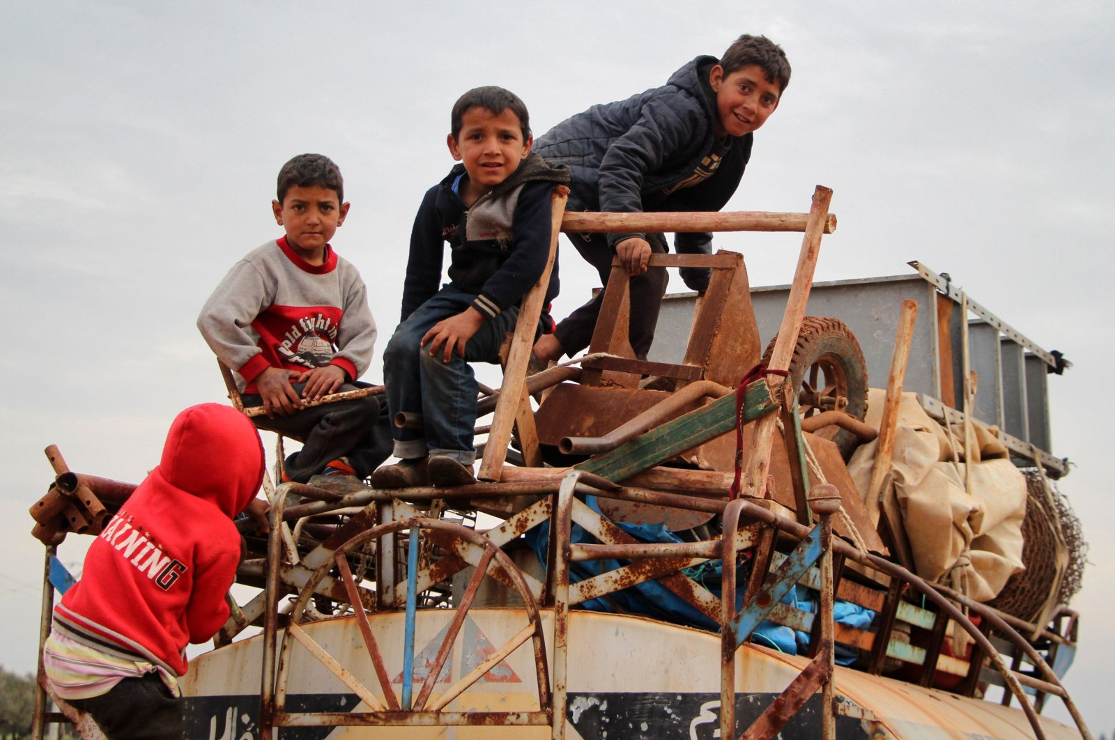 In this file photo taken on Feb. 15, 2020 children ride atop a water truck that is also loaded with furniture in the countryside of the village of Saharah, lying on the western edge of Syria's northern Aleppo province by Idlib province (AFP Photo)