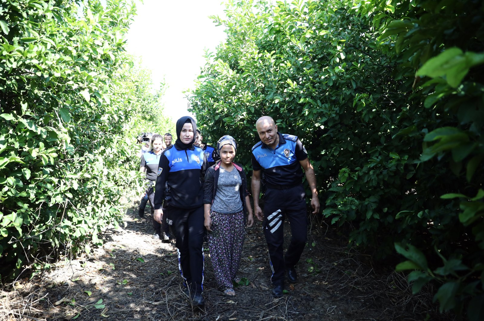 Police officers escort Fatma Poyraz – a child laborer working in an orchard with her family – to school in Adana, Turkey, October 8, 2019. (PHOTO BY ZİYA RAMOĞLU)