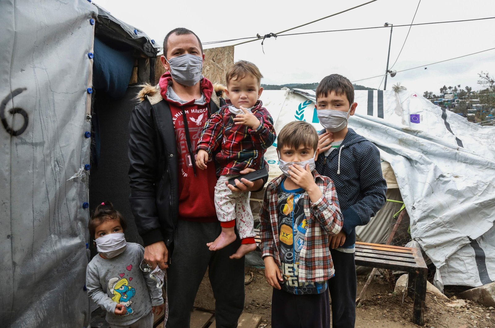 A migrant family wearing handmade protective face masks stand next to their tent in the camp of Moria in the island of Lesbos, Saturday, March 28, 2020. (AFP)