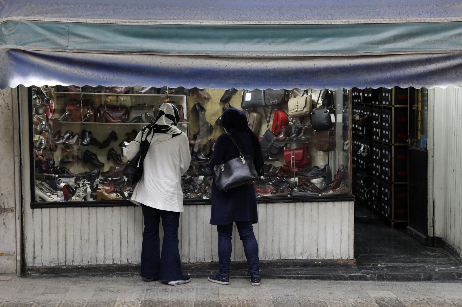 Two women look at shoes of a shop in a mostly empty street in a commercial district in downtown Tehran, Iran, Sunday, March 22, 2020. (AP Photo)