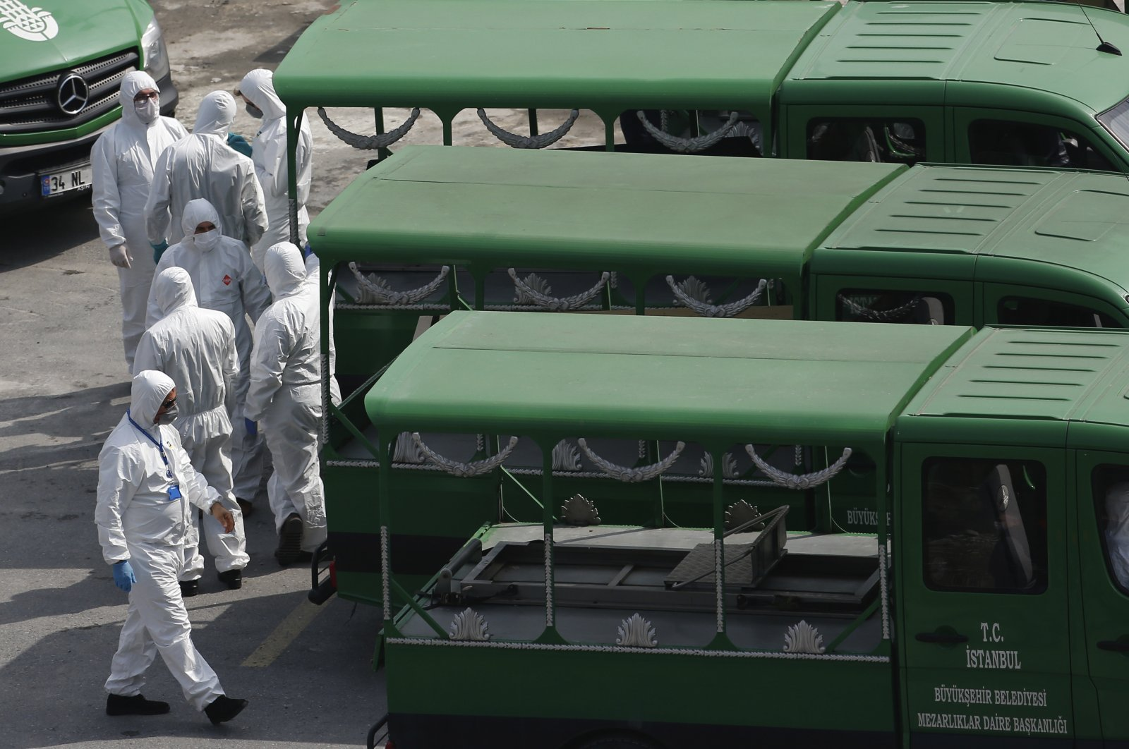 Officials wearing protective face masks and suits as a preventive measure against the spread of the coronavirus wait to load coffins of victims of Covid-19, to hearse trucks outside a morque in Istanbul, Monday, March 30, 2020. (AP Photo)