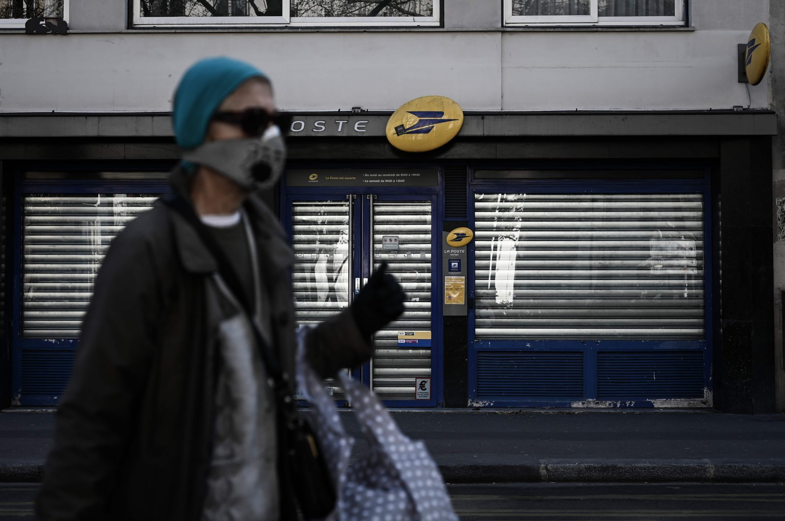 A woman wearing a protective face mask walks past a closed post office in Paris on March 31, 2020 on the 15th day of a strict lockdown in France aimed at curbing the spread of the COVID-19 infection, caused by the novel coronavirus. (AFP Photo)