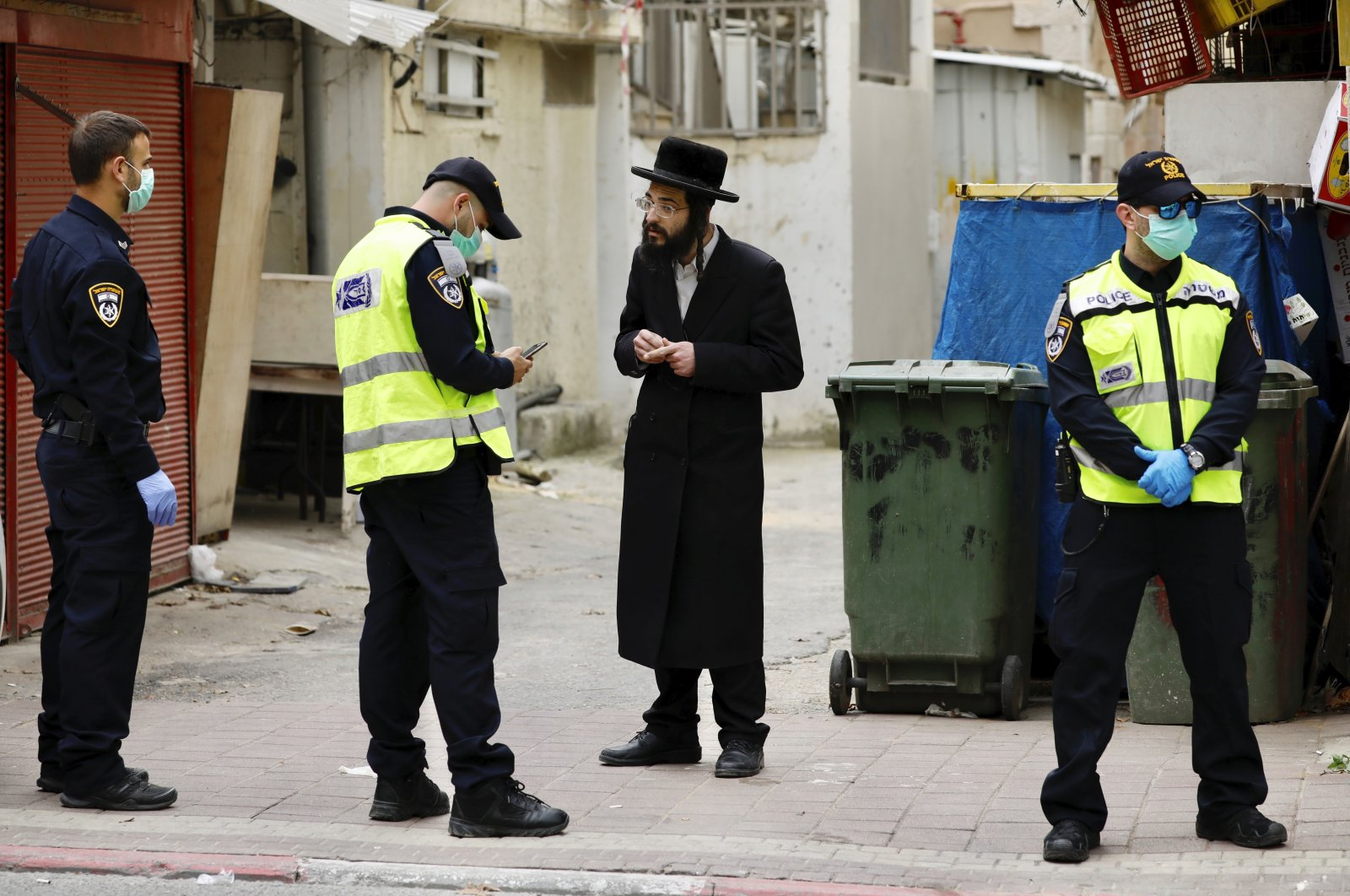 An ultra-Orthodox Jewish man is questioned by an Israeli police officer as part of the government's measures to stop the spread of the coronavirus, in the Orthodox city of Bnei Brak, a suburb of Tel Aviv, Israel, Tuesday, March 31, 2020. (AP Photo)