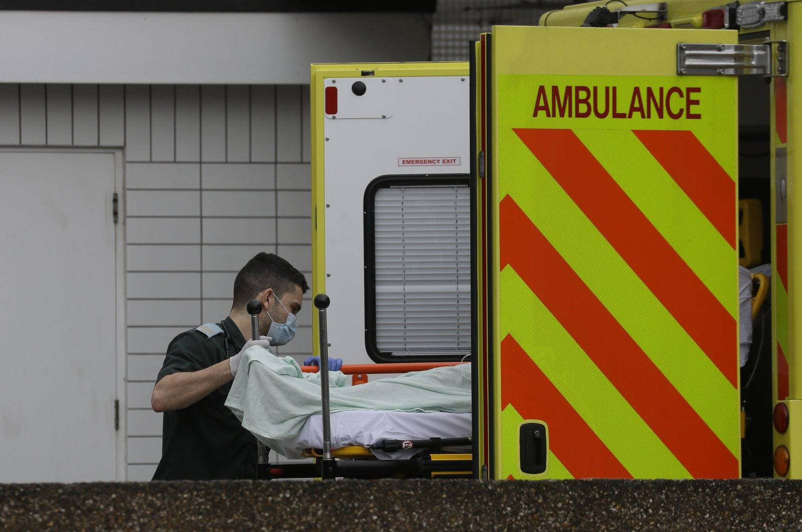 A patients is helped from an ambulance as they arrive at St Thomas' Hospital, one of may hospitals that are in the front line of the coronavirus outbreak, in London, Tuesday, March 31, 2020. (AP Photo)