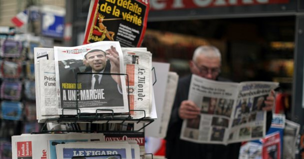 A man reads the local newspaper near a rack which displays copies of French daily newspapers with front pages about the results in France's Presidential election in Nice April 24, 2017. (REUTERS Photo)