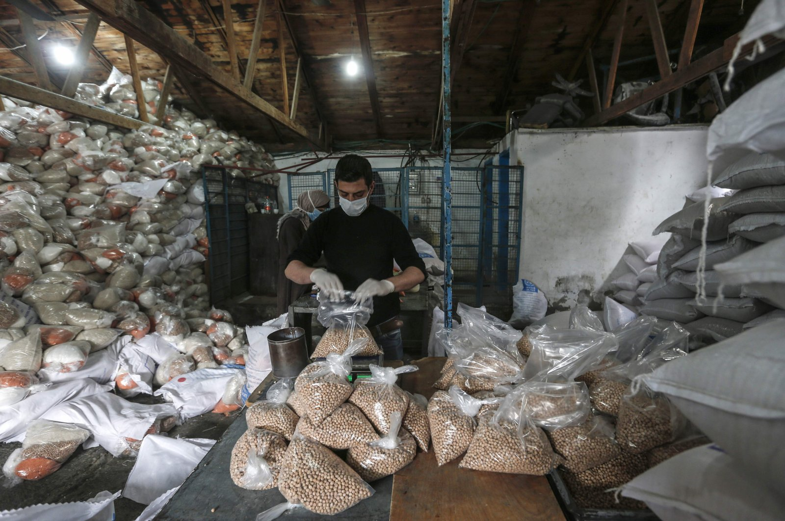 Palestinian employees at the United Nations Relief and Works Agency for Palestinian Refugees (UNRWA) wearing protective masks and gloves prepare food aid rations to be delivered to refugee family homes rather than distributed at a U.N. center, in Gaza City, Tuesday, March 31, 2020. (AFP Photo)