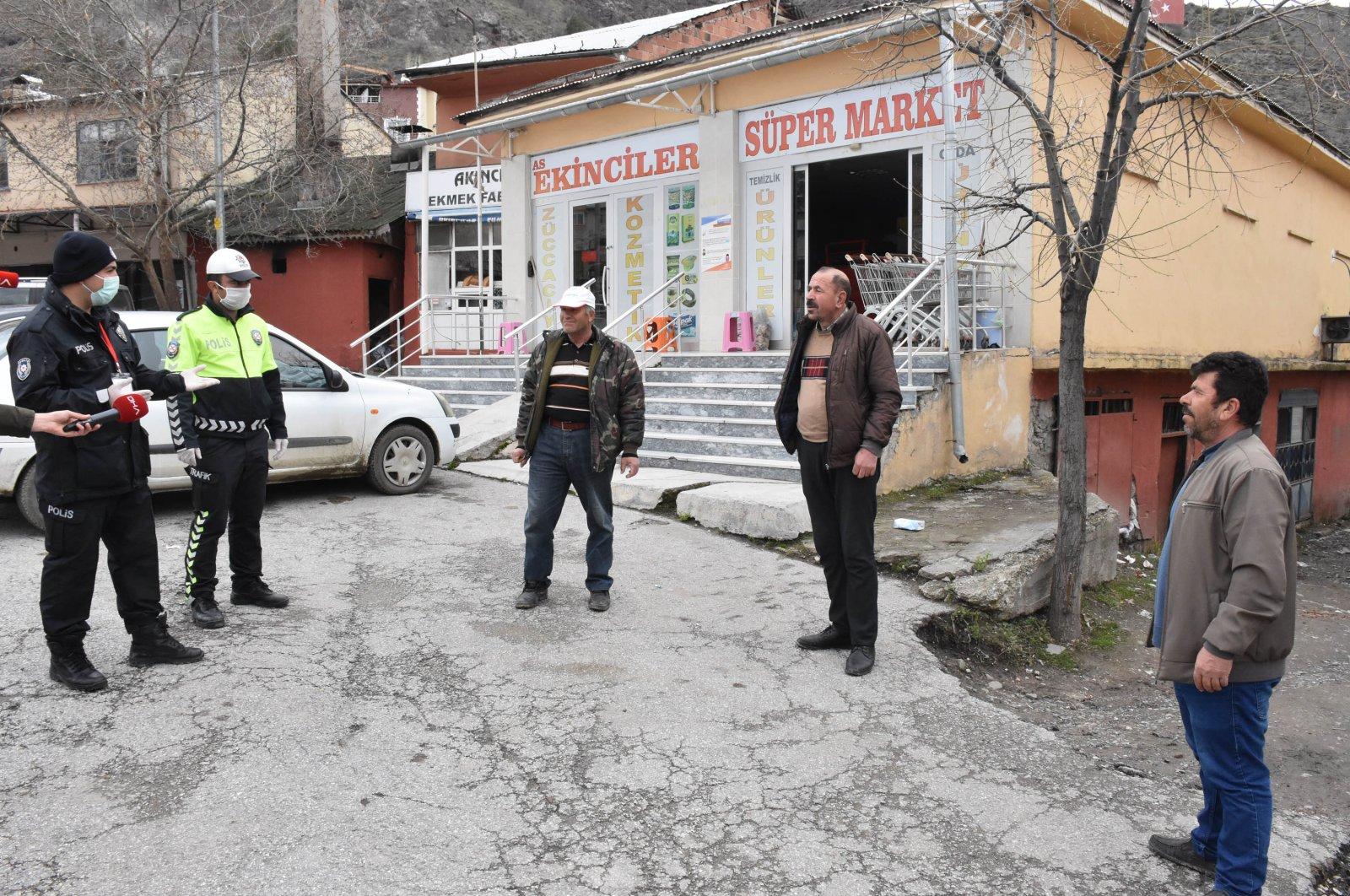 Police officers warn three men caught walking too close together, in Akıncılar, Sivas, Turkey, Wednesday, April 1, 2020. (DHA Photo)