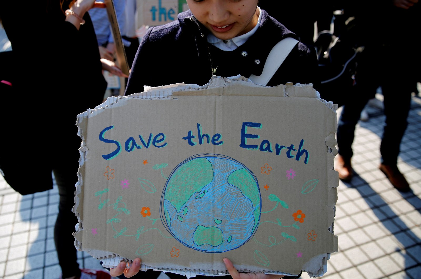 A school student holds a sign as she takes part in the global students strike for action on climate change in Tokyo, Japan, March 15, 2019. (Reuters Photo)