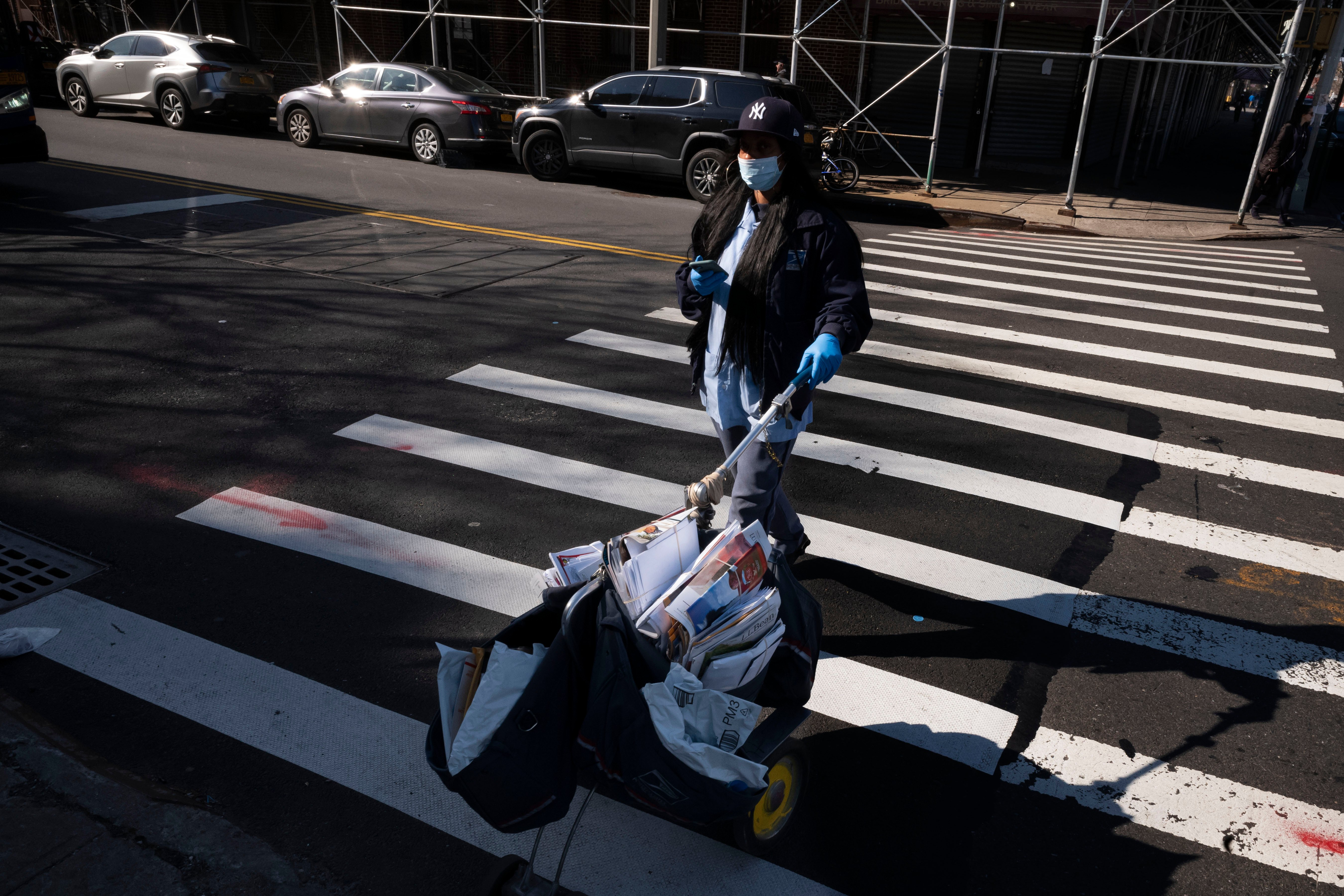In this Thursday, March 26, 2020 photo, a postal worker wears a mask and gloves as she delivers the mail in the Brooklyn borough of New York. (AP Photo)