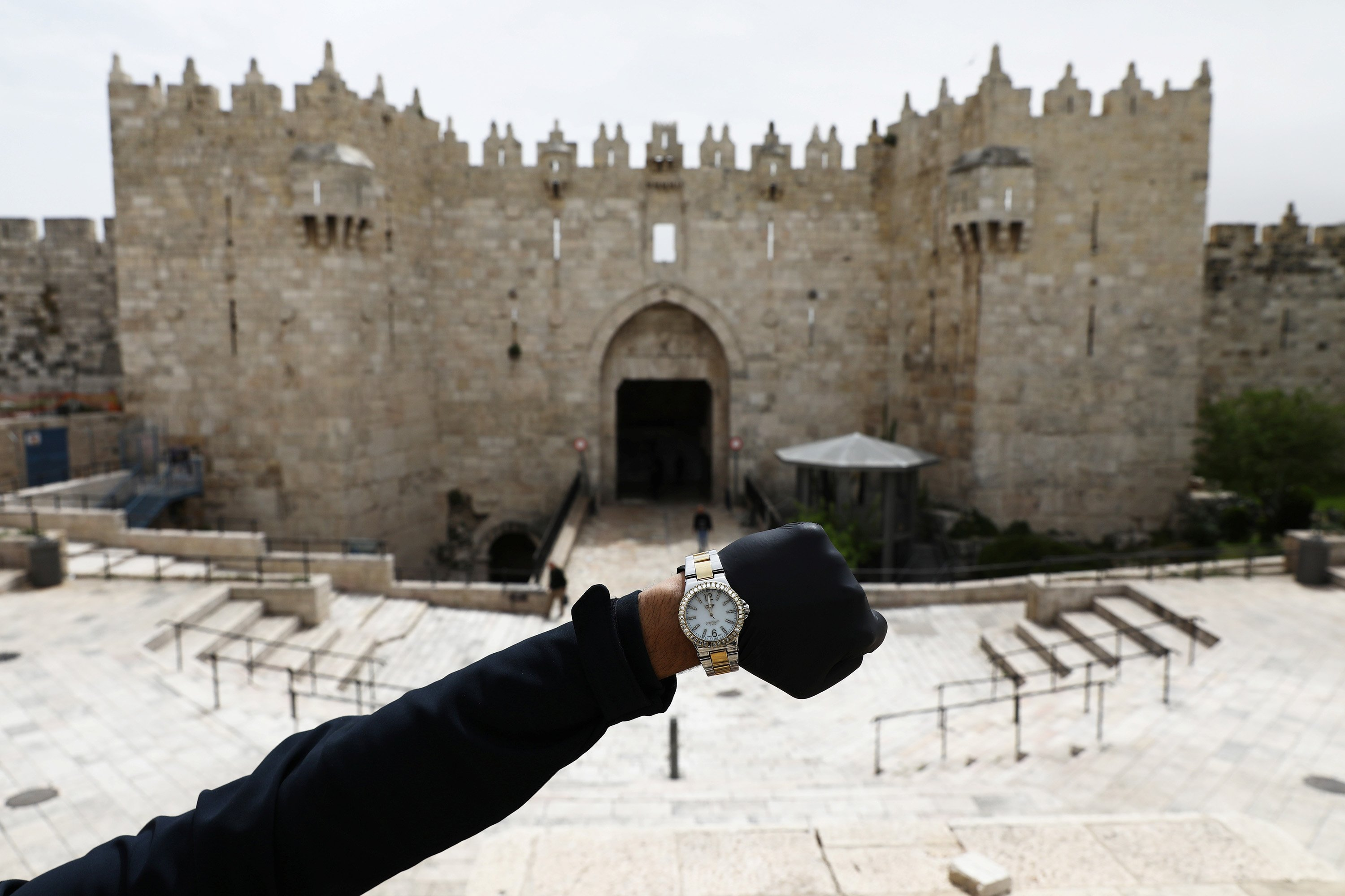 A watch showing the time at noon in front of Damascus Gate, as it is in front of an empty staircase at Jerusalem's Old City, March 31, 2020. (Reuters Photo)