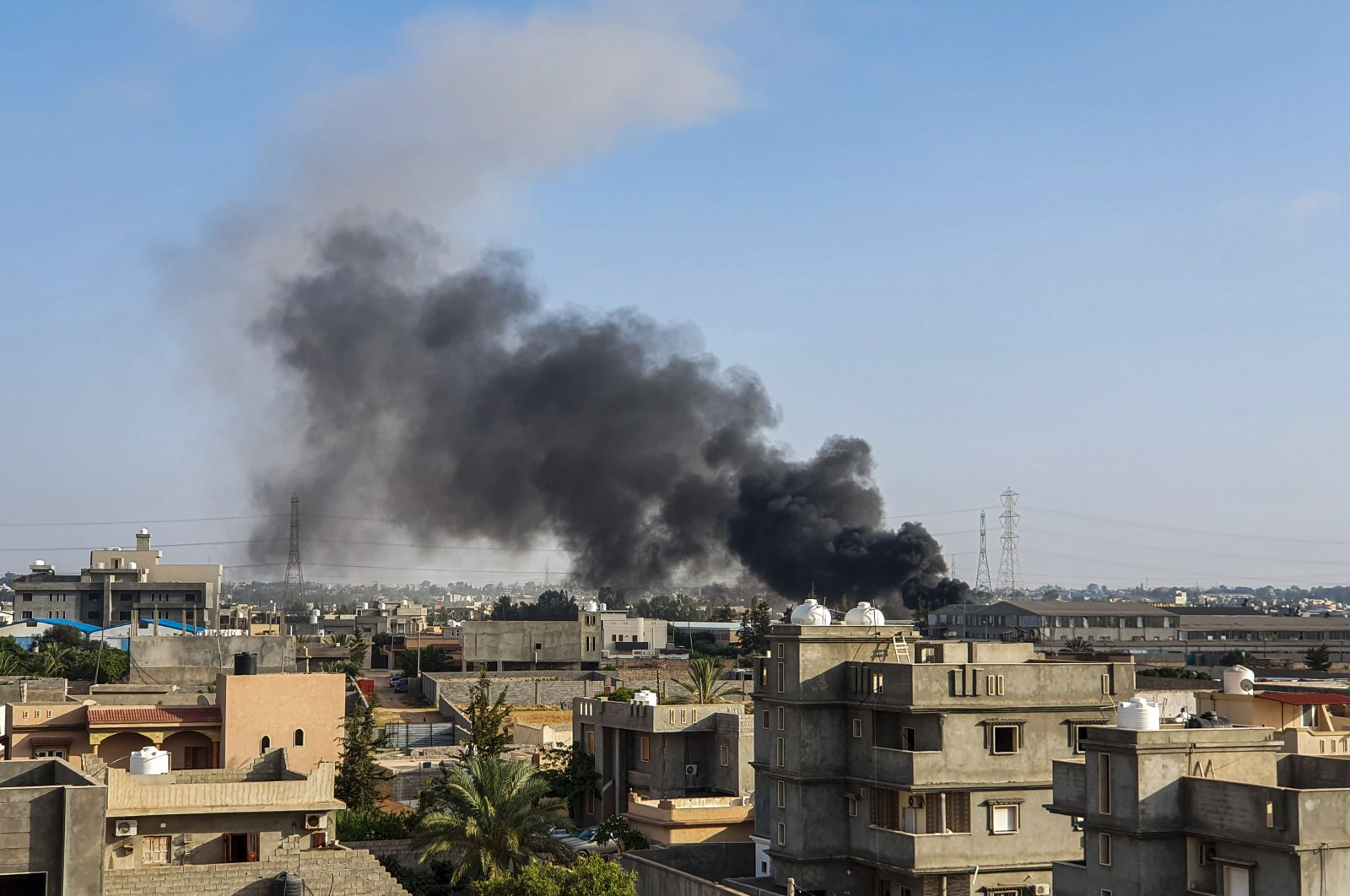 This picture taken on June 29, 2019, shows smoke plumes rising in Tajoura, south of the Libyan capital Tripoli, following a reported airstrike by forces loyal to putschist general Khalifa Haftar. (AFP Photo)