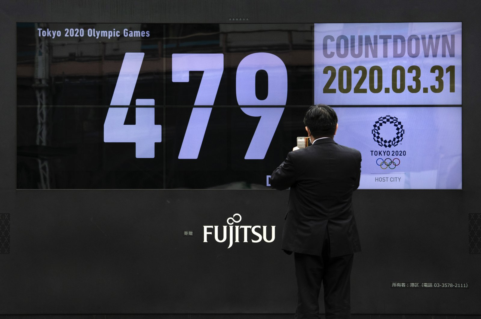 A man takes pictures of a countdown display for the Tokyo 2020 Olympics after it was restarted following the decision to postpone the Games, Tuesday, March 31, 2020, in Tokyo. (AP Photo)