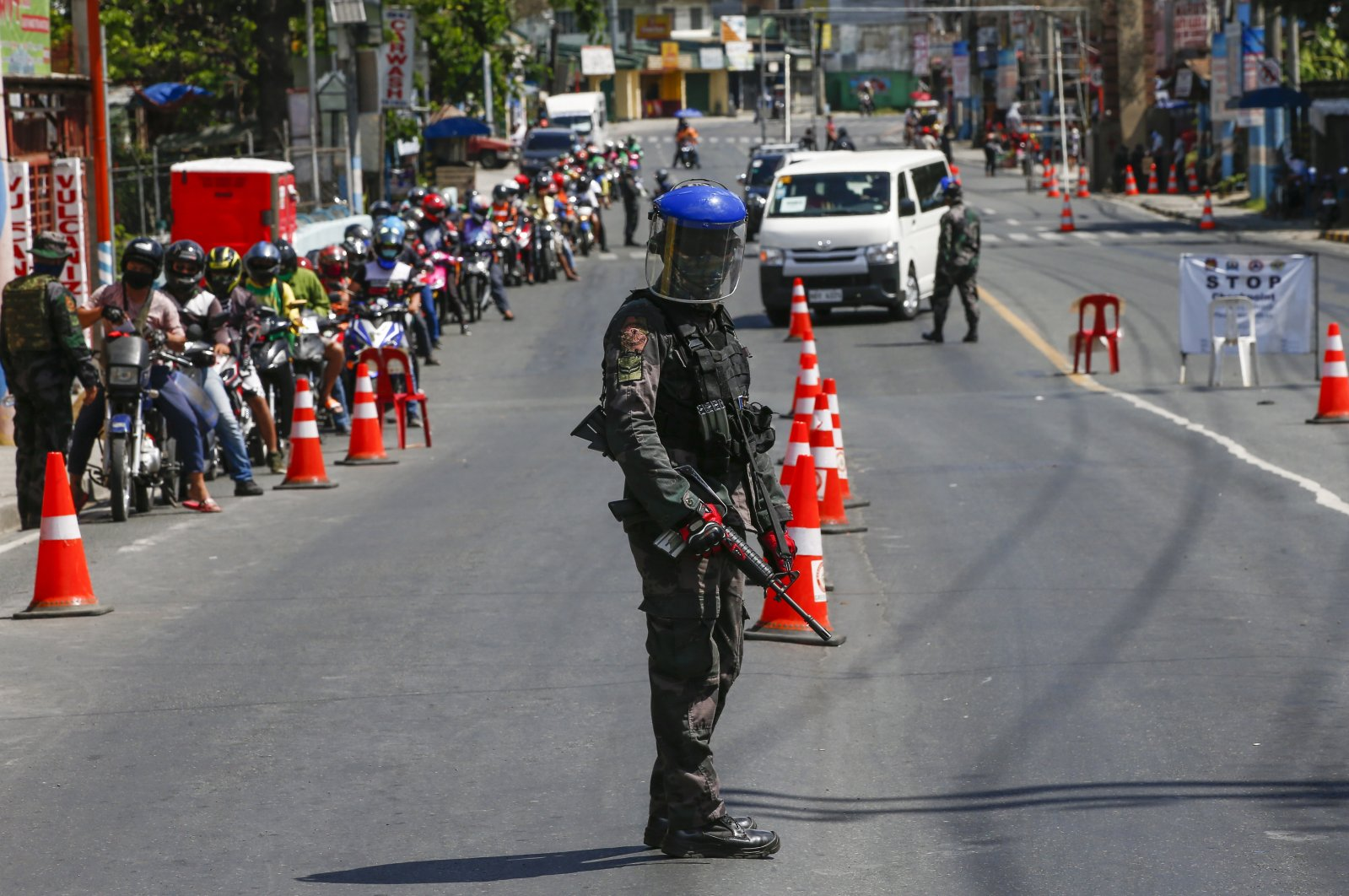 A police officer guards a checkpoint at the border between Rizal province and Marikina City, Metro Manila, Philippines, Thursday, April 2, 2020. (EPA Photo)