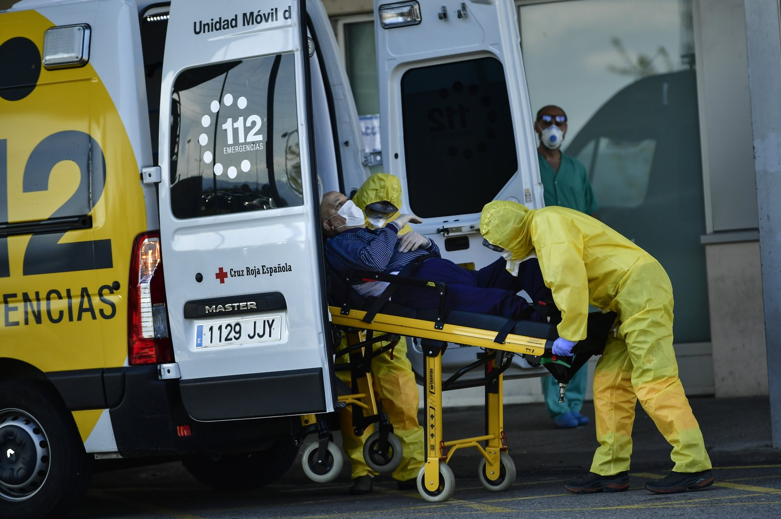 Staff health medical ambulances wearing special equipment to prevent the spread of coronavirus COVID-19 arriving with a patient at San Pedro hospital, in Logrono, northern Spain, Saturday, March 28, 2020. (AP Photo)
