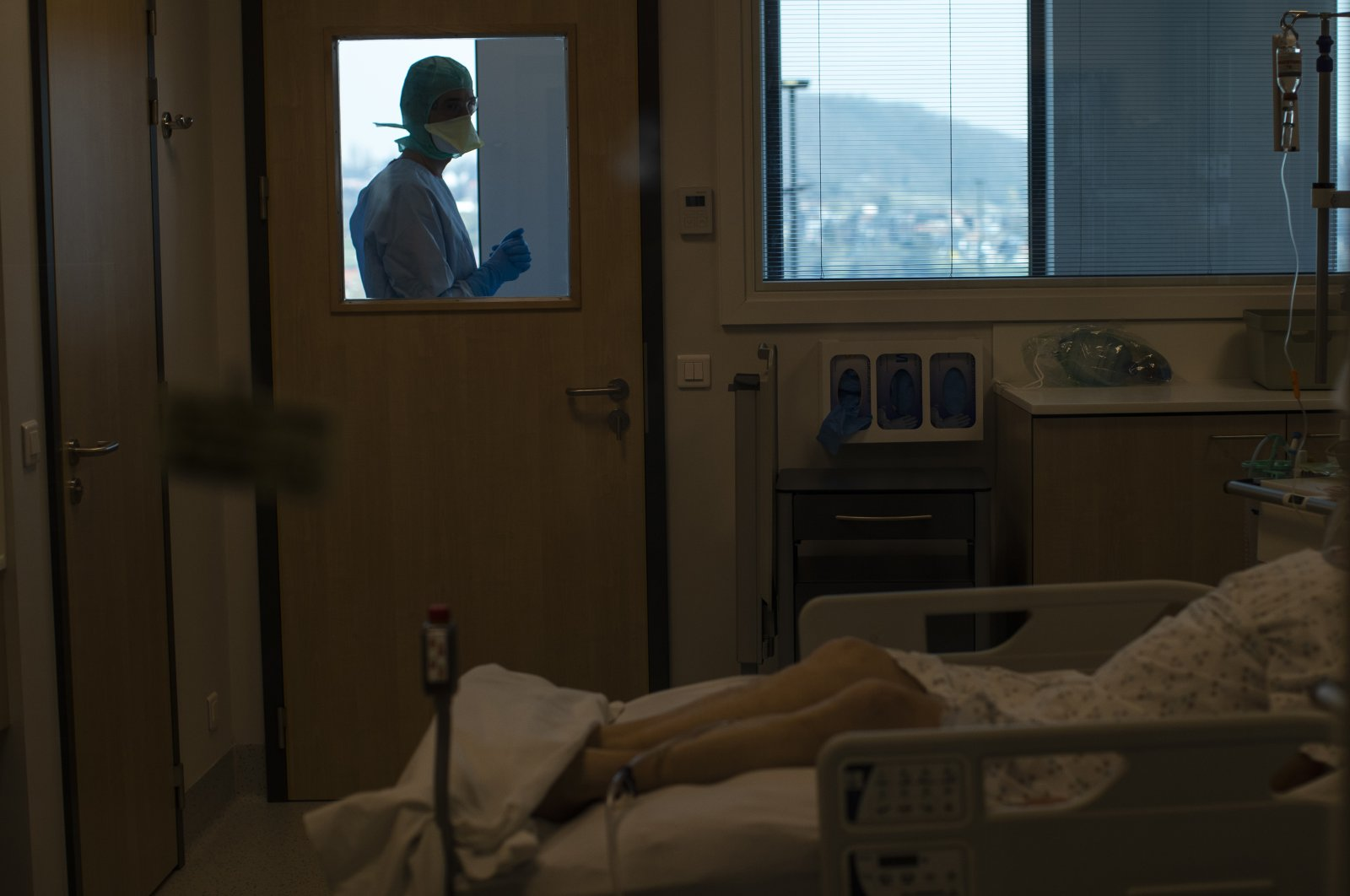 In this photograph taken from behind a window, medical personnel work in the intensive care ward for COVID-19 patients at the MontLegia CHC hospital in Liege, Belgium, Friday, March 27, 2020. (AP Photo)
