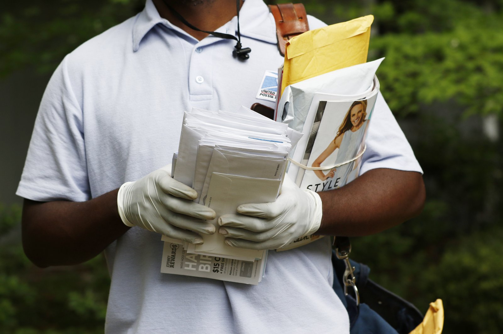 A postal service carrier dons gloves as he delivers mail in northeast Jackson, Miss., Monday, March 30, 2020. (AP Photo)
