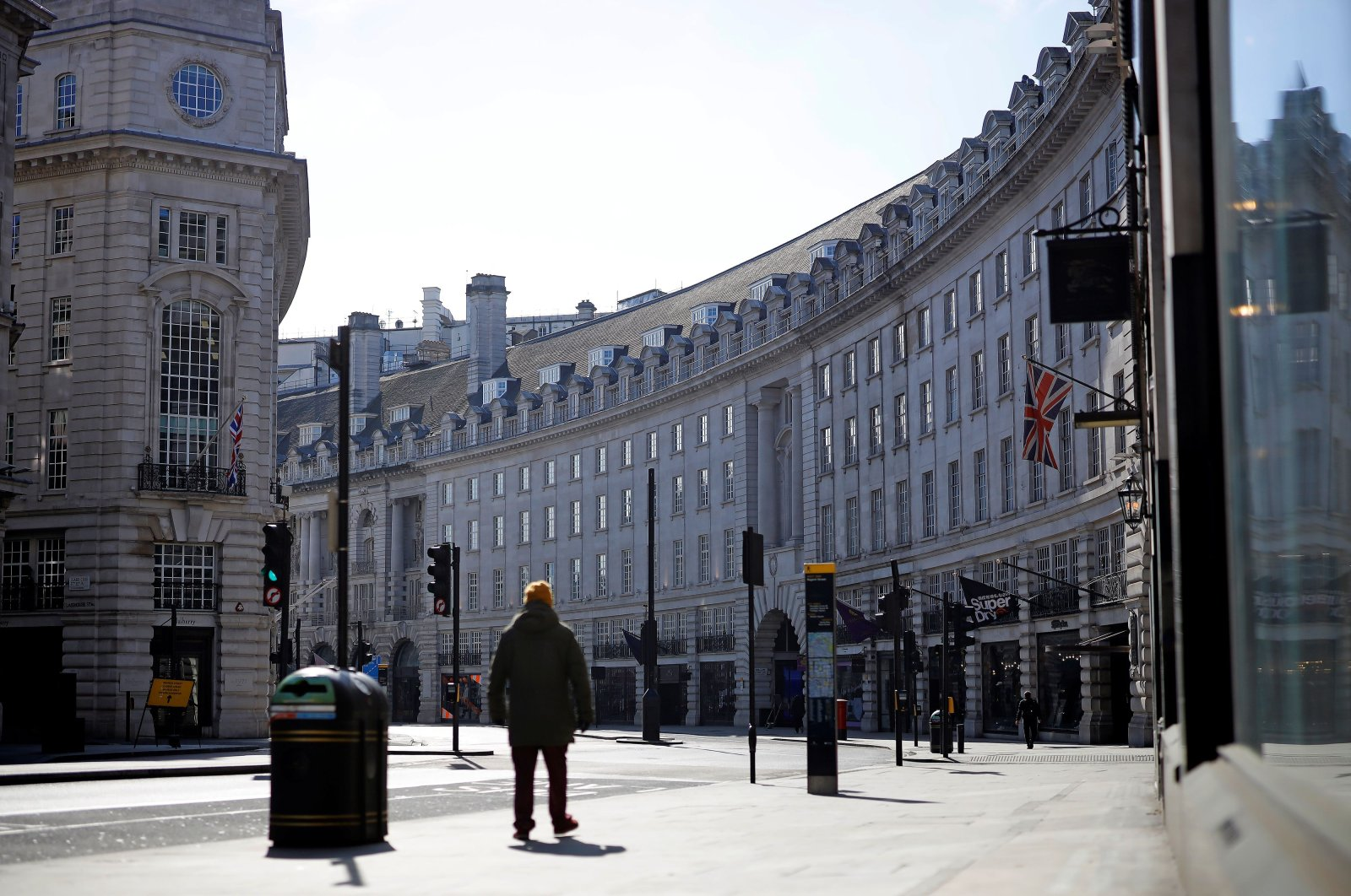 A man walks past closed-down shops on an empty Regent Street in London on Thursday, April 2, 2020, as life in Britain continues during the nationwide lockdown to combat the novel coronavirus pandemic. (AFP Photo)