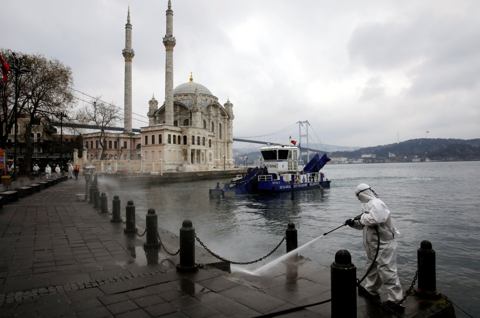A worker sprays disinfectant outside Ortakoy Mosque, to prevent the spread of the new coronavirus disease (COVID-19), in Istanbul, Turkey, March 23, 2020. (Reuters Photo)