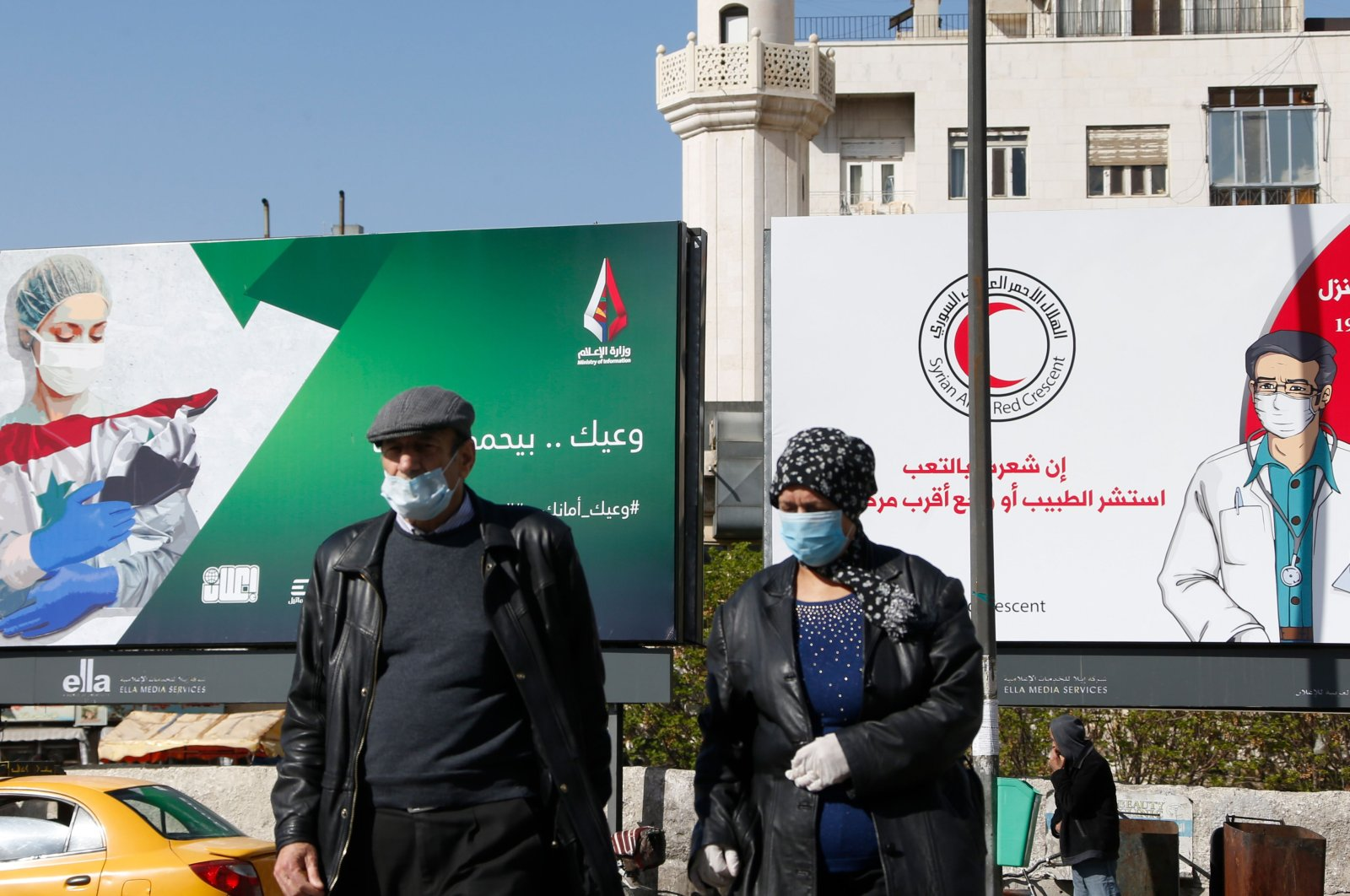 Syrians wearing face masks walk in front of posters informing about the coronavirus, in the capital Damascus, Wednesday, April 1, 2020. (AFP)