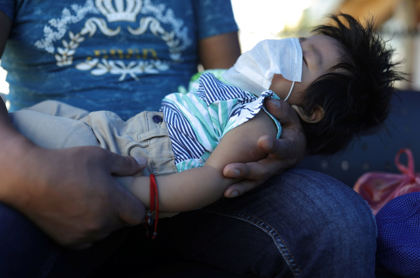 A man holds a baby wearing a protective mask during a quarantine following the outbreak of coronavirus disease (COVID-19), in Santiago, Chile, Wednesday, April 1, 2020. (Reuters Photo)
