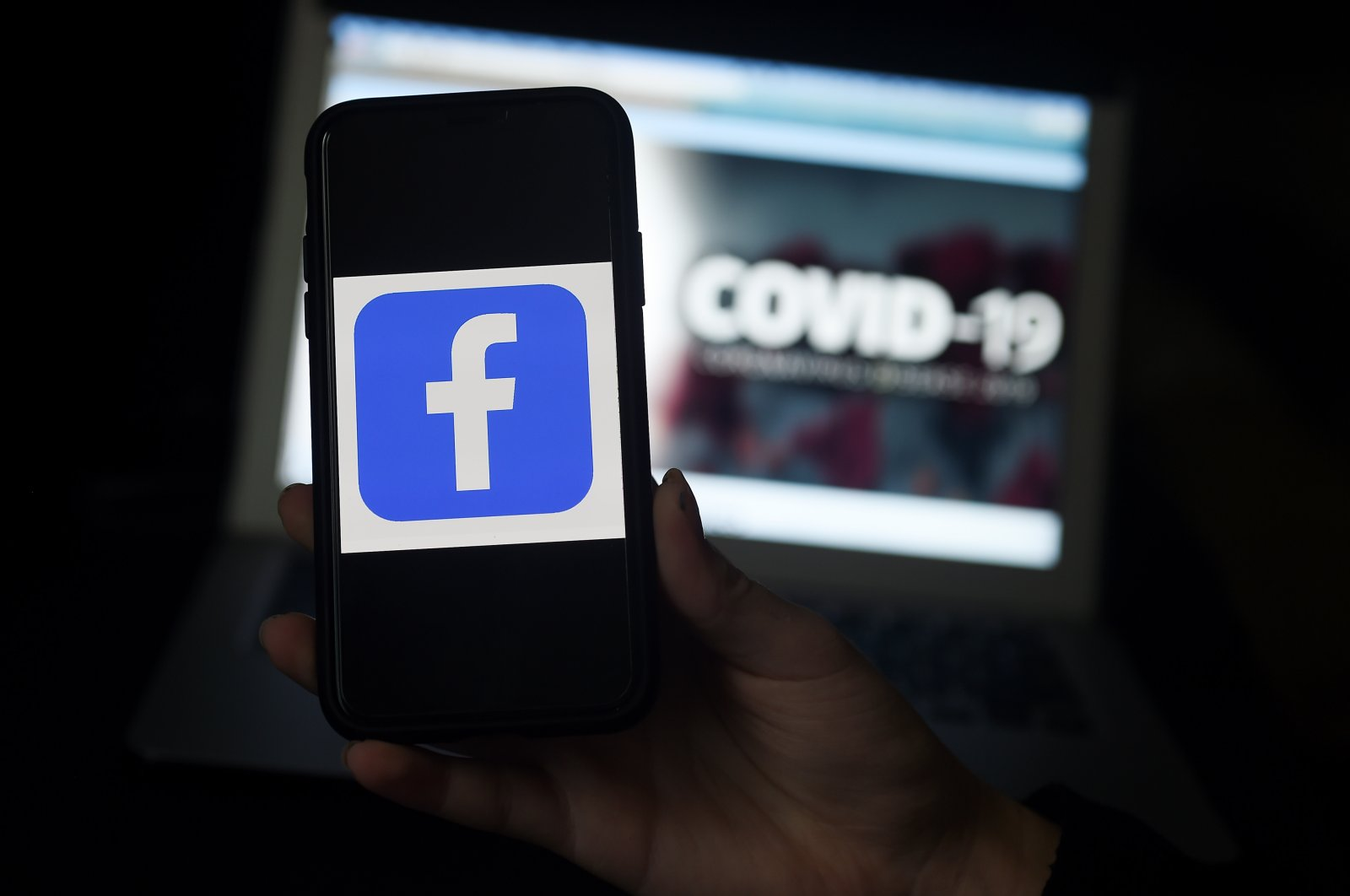 In this file photo, the Facebook logo is displayed on a mobile phone screen photographed on a COVID-19 illustration graphic background in Arlington, Virginia on March 25, 2020. (AFP Photo)