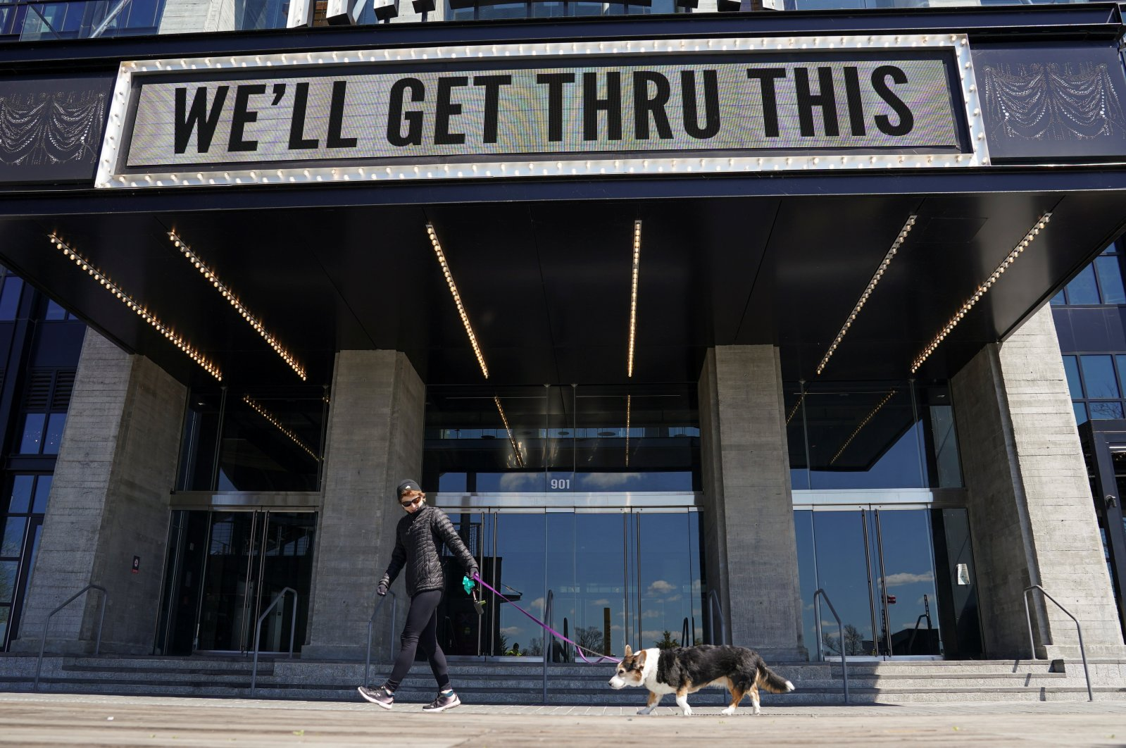 """A woman walks her dog under the marquee at The Anthem music venue reading """"We'll Get Thru This"""" referring to the battle against the coronavirus disease (COVID-19) pandemic, in Washington, U.S., Thursday, April 2, 2020. REUTERS"""