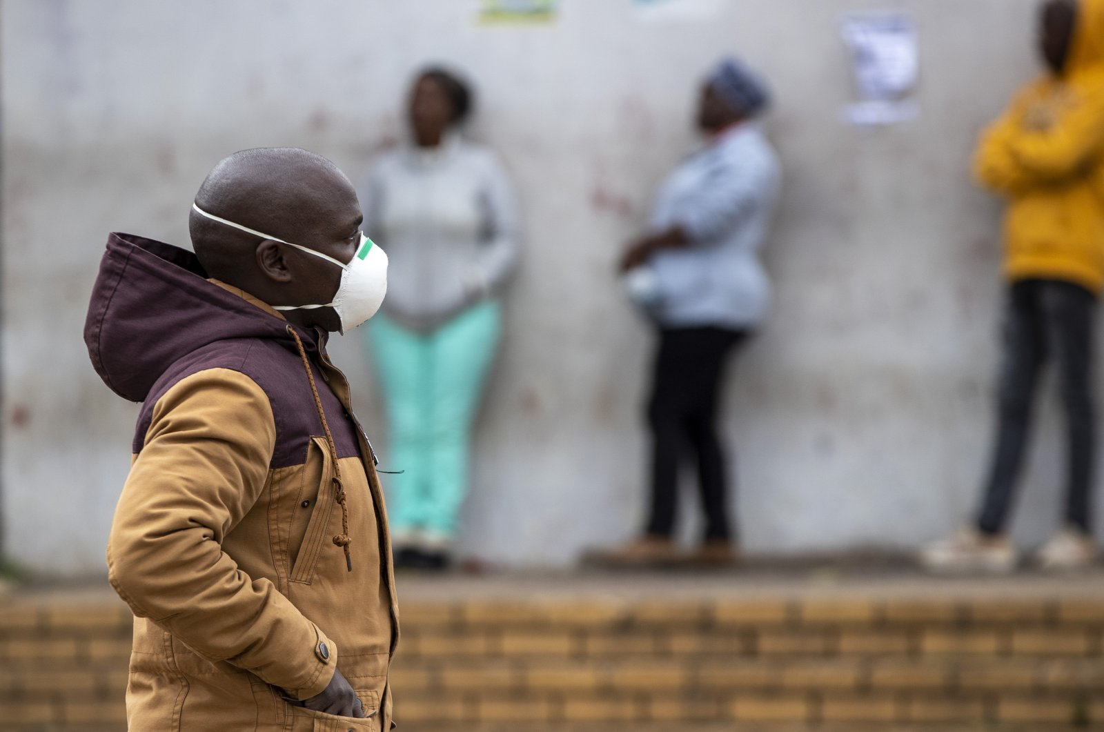 A man wearing face masks to protect himself against coronavirus, walks past people queuing for shopping in Duduza, east of Johannesburg, South Africa, Thursday, April 2, 2020.  (AP Photo)