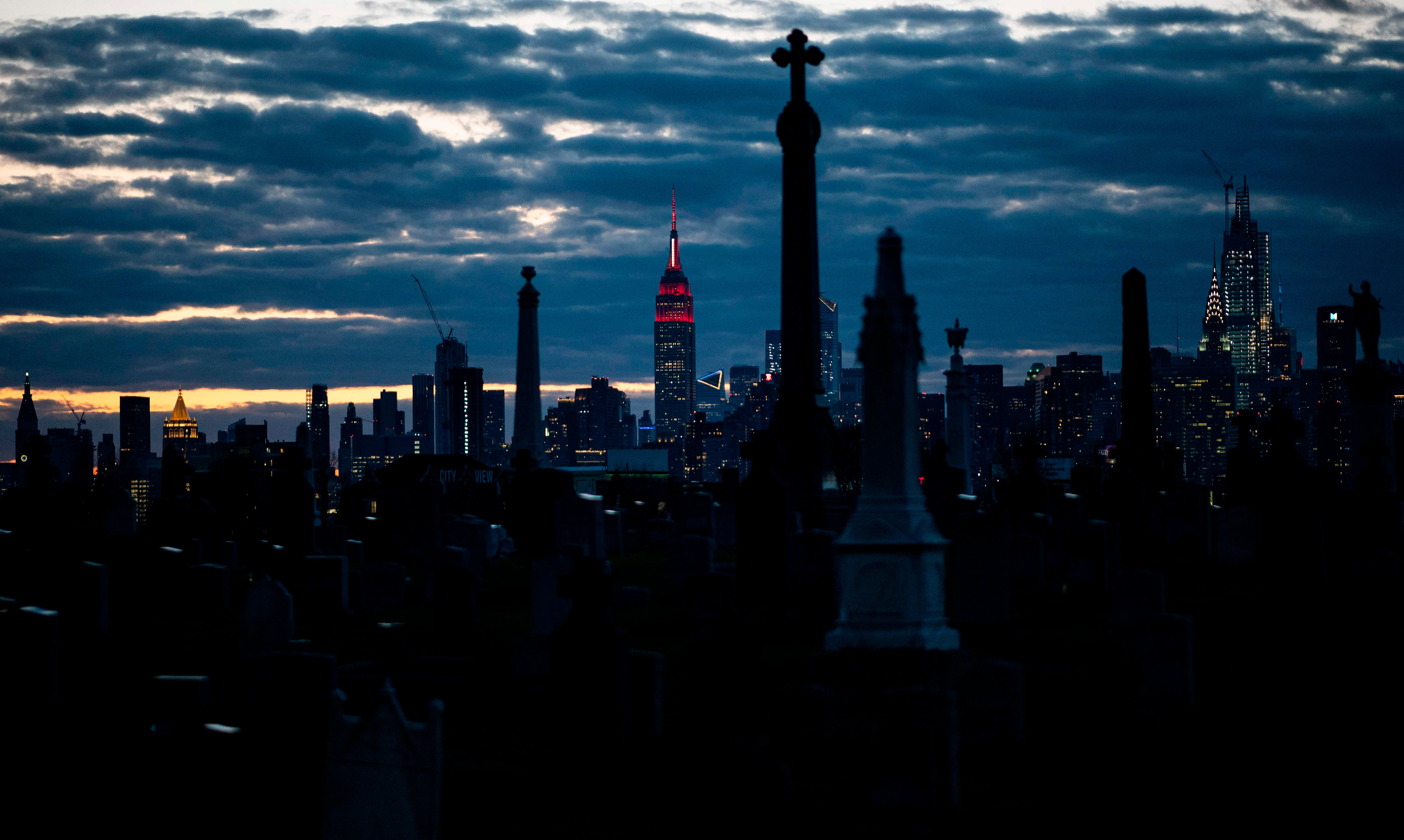The Empire State Building, seen behind the Calvary Cemetery, is lit with a white and red 'siren' in its mast to pay tribute to medical workers battling the coronavirus outbreak on Wednesday, April 1, 2020 in New York City. (AFP Photo)