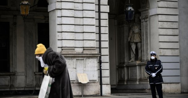 An elderly woman walks past a policeman during a minute of silence at noon in Turin as flags are being flown at half-mast in cities across Italy to commemorate the victims of the virus, Tuesday,  March 31, 2020. (AFP)