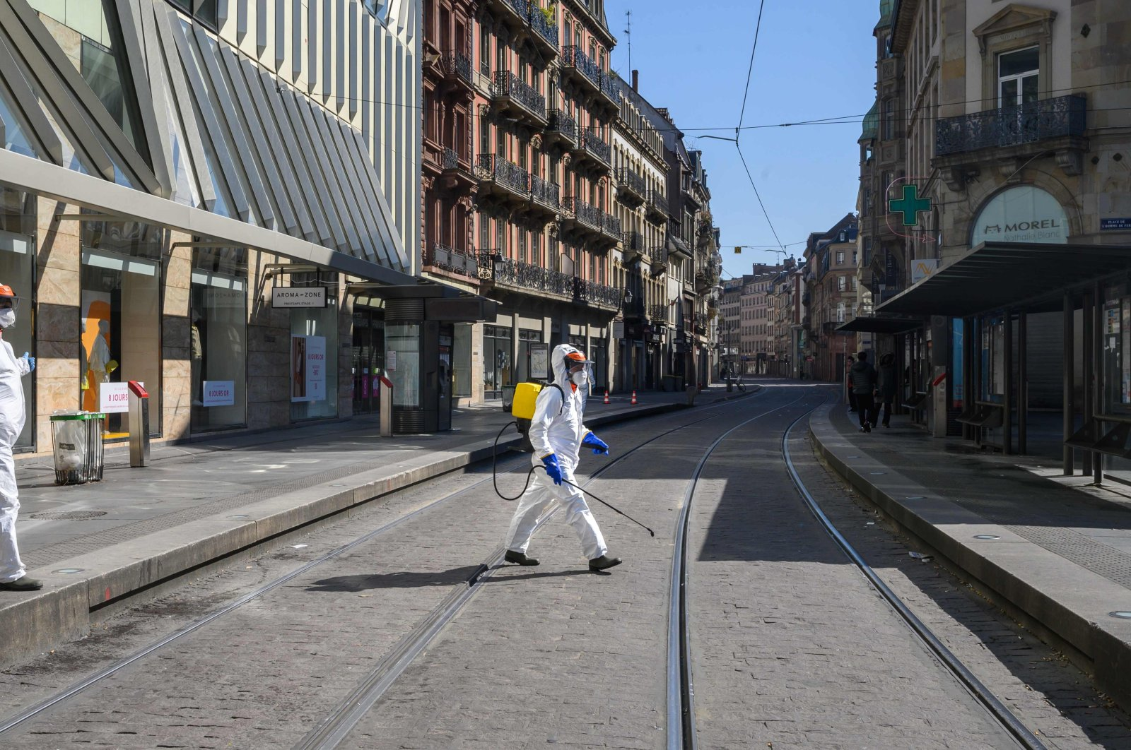 An employee wearing protective gear sprays disinfectant at a tram station in central Strasbourg on April 1, 2020, on the 16th day of a lockdown aimed at curbing the spread of the coronavirus. (AFP Photo)