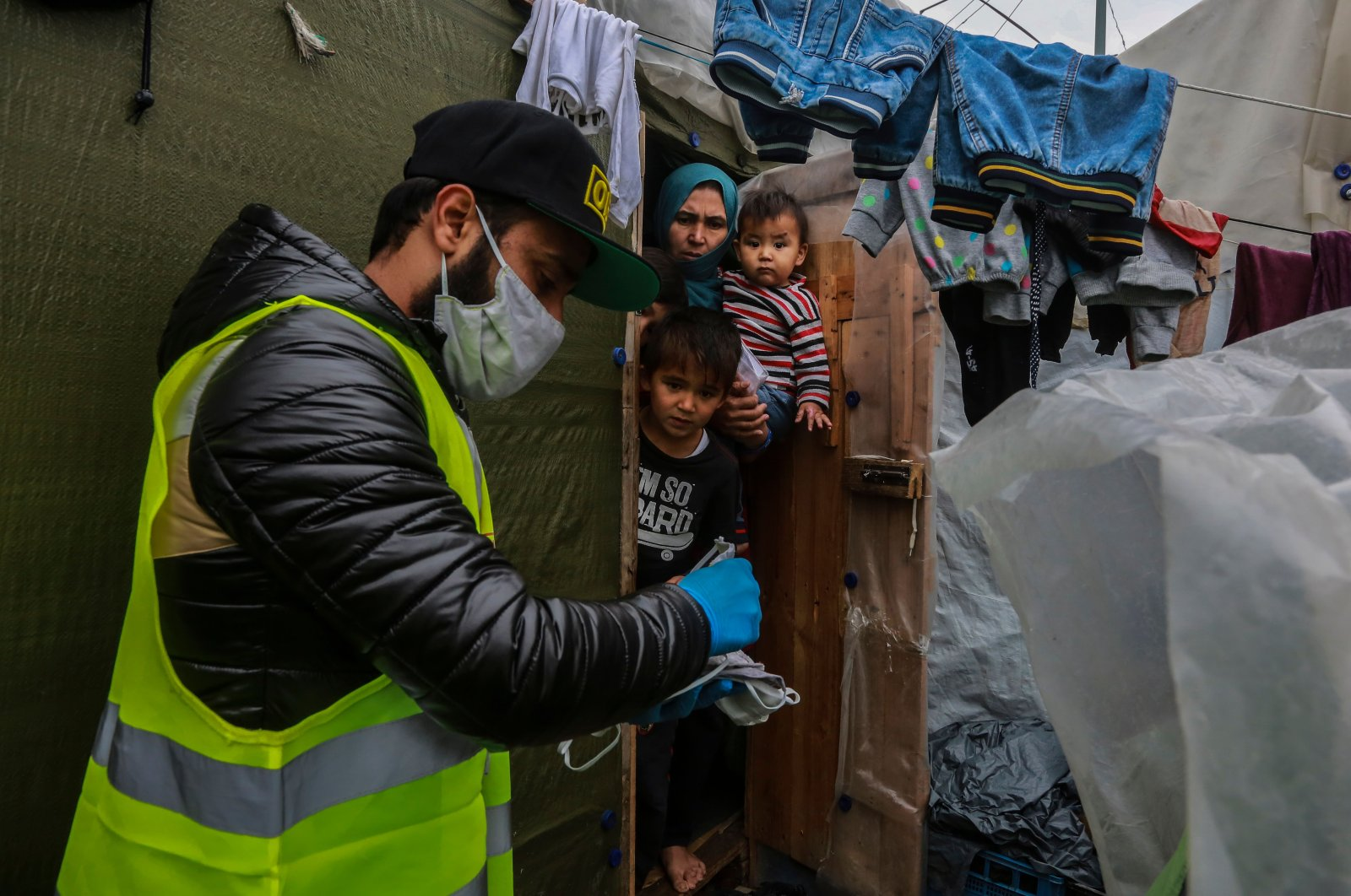 """A member of nongovernmental organization """"Team Humanity"""" shares handmade protective face masks with migrants and refugees in the camp of Moria on the island of Lesbos on Saturday, March 28, 2020 (AFP Photo)"""