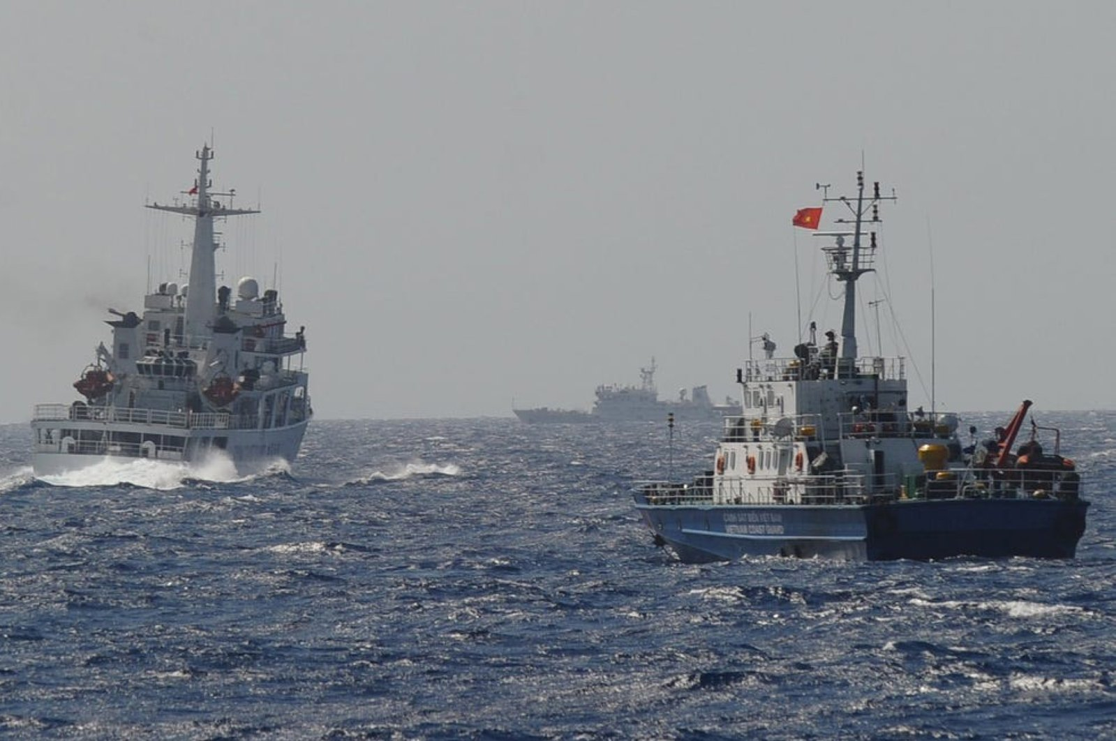 This picture taken on May 14, 2014 shows a Chinese coast guard vessel (C) followed by a Vietnamese coast guard ship near the area of China's oil drilling rig in disputed waters in the South China Sea. (AFP Photo)