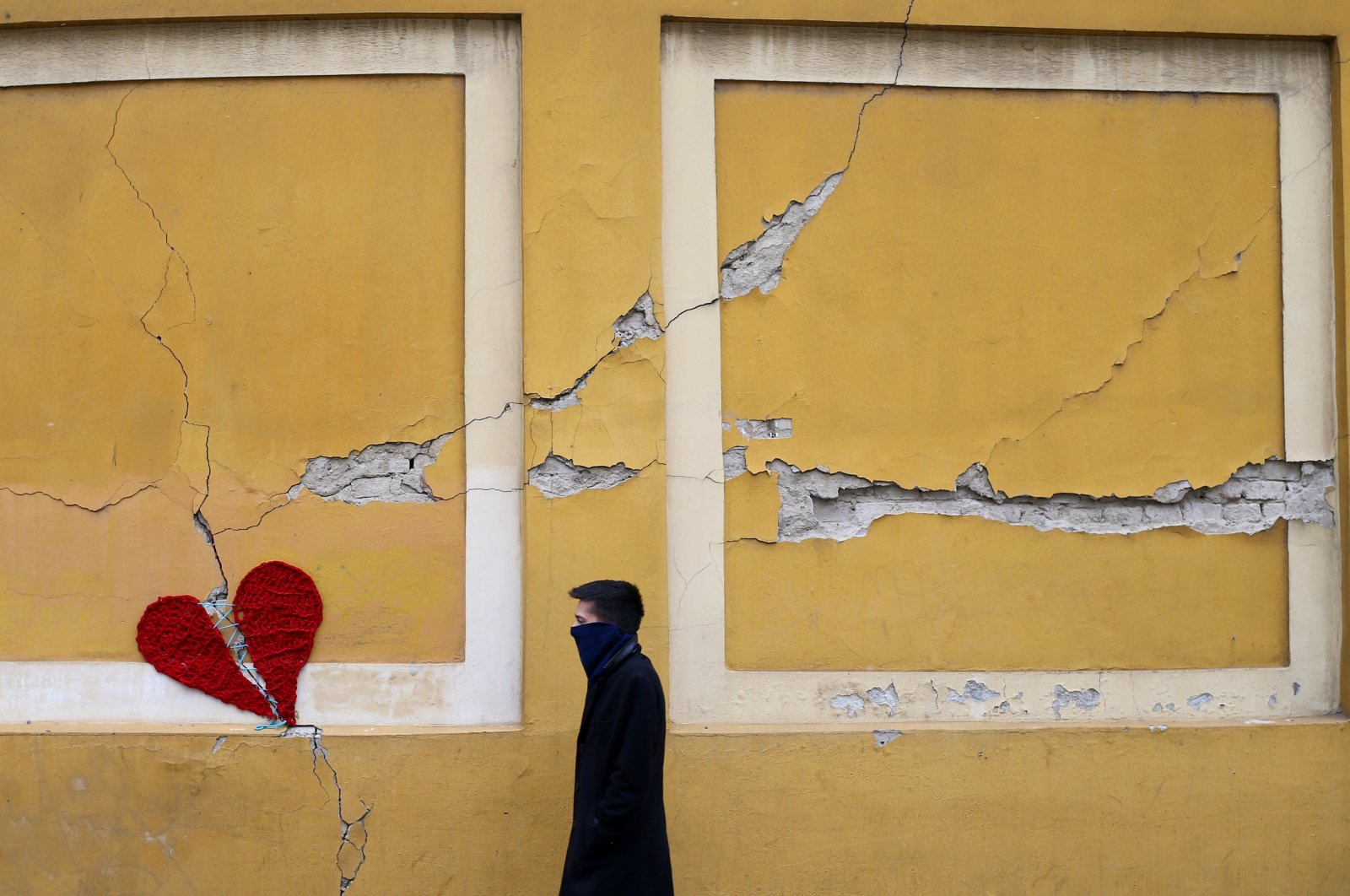 A man walks next to a repaired broken heart made of wool by Croatian designer Ivona, put on a building in downtown Zagreb, Croatia, Tuesday, March 25, 2020. (REUTERS Photo)