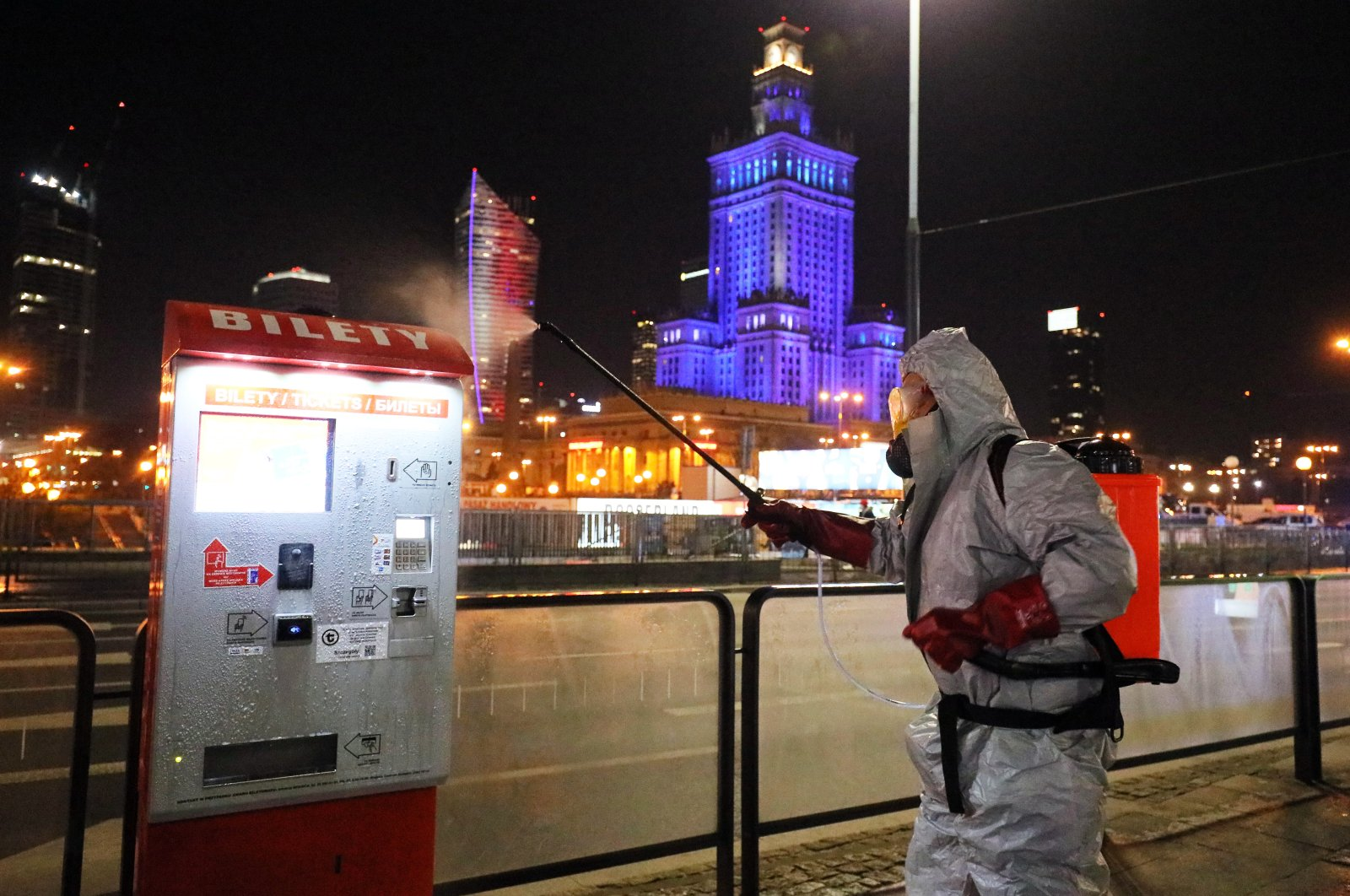 A worker wearing a protective suit sprays disinfectant at a tram station in Warsaw, Poland, April 2, 2020, amid the ongoing coronavirus COVID-19 pandemic. (EPA Photo)