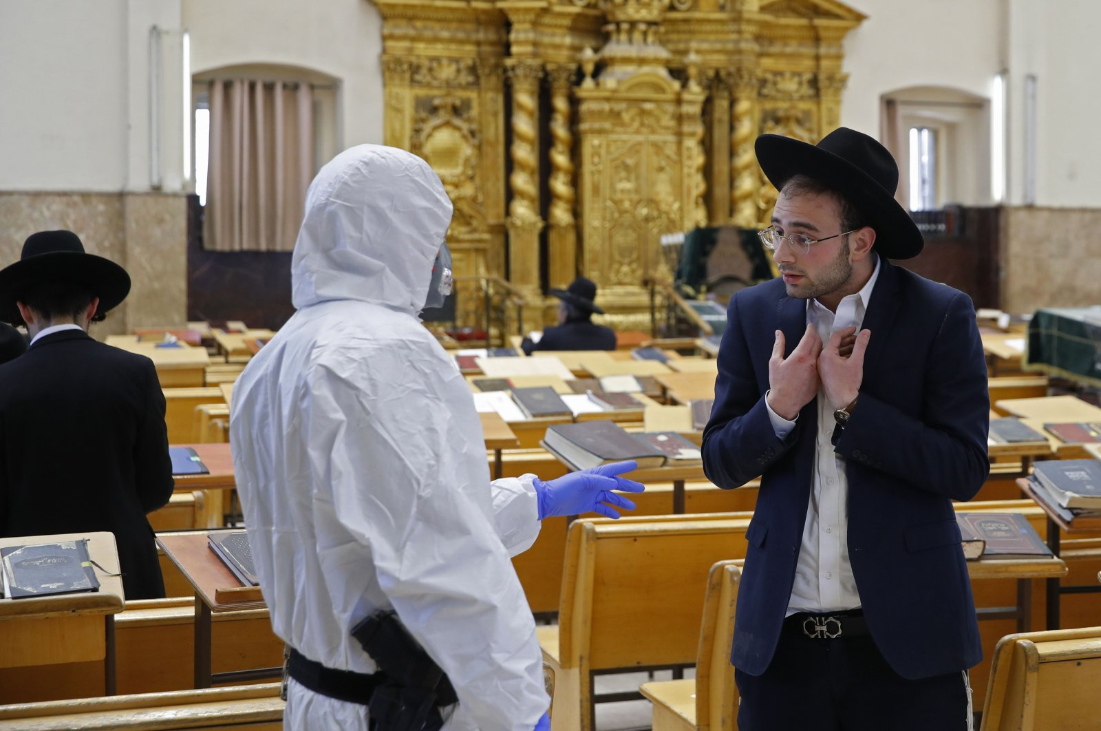 An Israeli police officer, dressed in a protective outfit, speaks to a Yeshiva (Jewish educational institution for studies of traditional religious texts) student, in the Israeli city of Bnei Brak on Thursday, April 2, 2020, during a control to enforce social distancing measures imposed by Israeli authorities to curb the spread of the novel coronavirus. (AFP Photo)