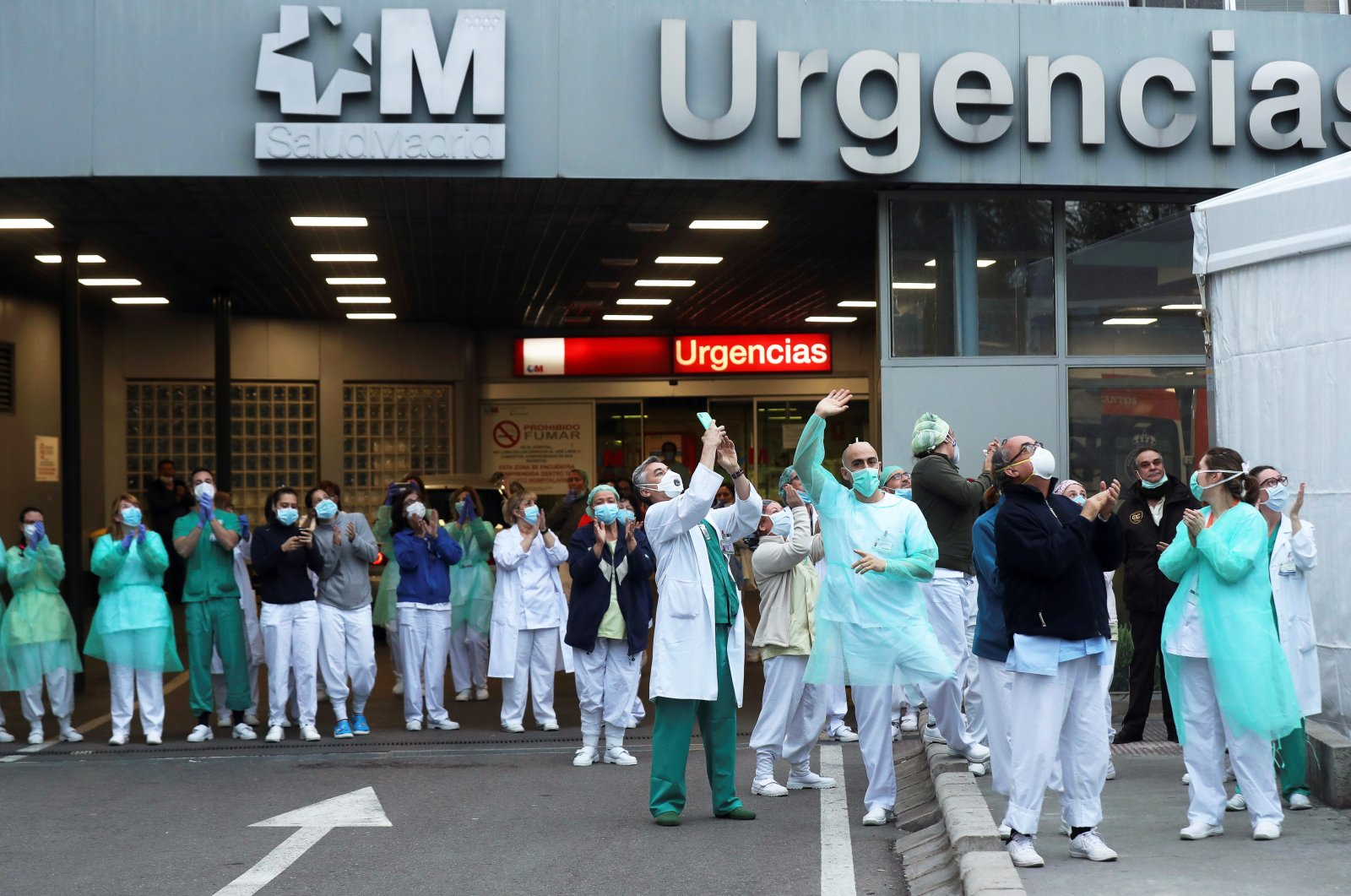 Health workers react as they take part in the nationwide daily gratitude applause to thank members of the sanitary personnel as well as the society in front of La Paz Hospital in Madrid, Spain, April 02, 2020. (EPA Photo)