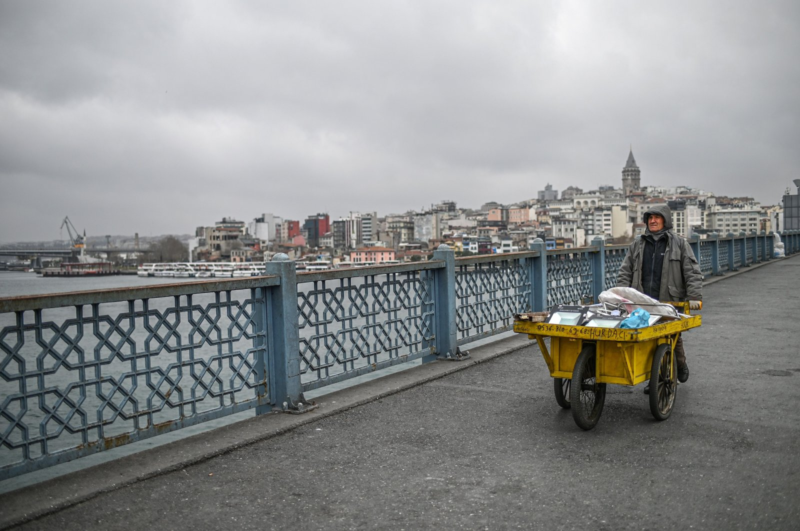 A garbage collector pushes a wheelbarrow across the empty Galata bridge in Istanbul, Wednesday, April 1, 2020 (AFP Photo)