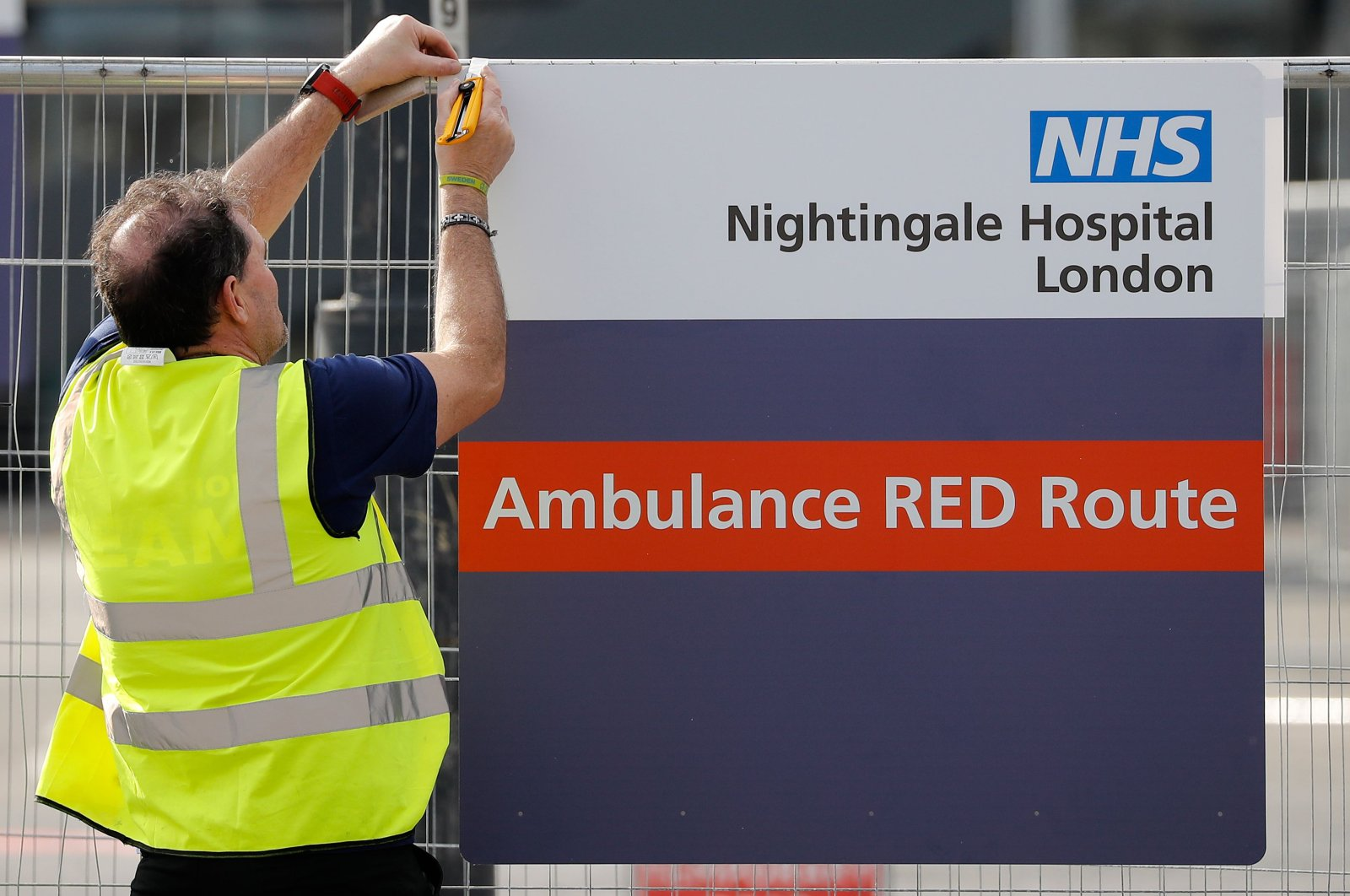 """A worker fixes a new sign to a fence at the ExCeL London exhibition center, which has been transformed into the """"NHS Nightingale"""" field hospital, to help with the novel coronavirus COVID-19 pandemic, in London on Friday, April 3, 2020. (AFP Photo)"""