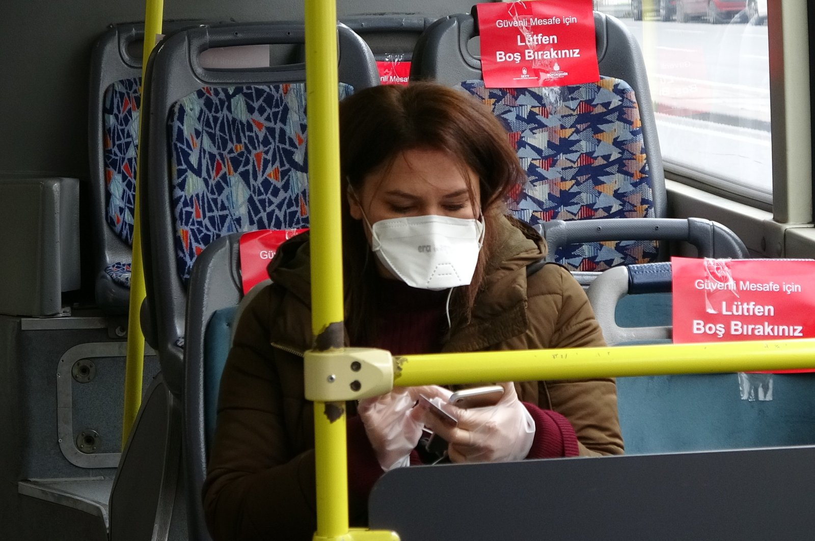 A woman wearing a mask sitting inside a bus in Istanbul, Turkey, Tuesday, March 31, 2020. (İHA Photo)
