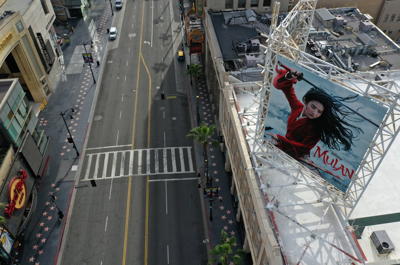 """A poster of the """"Mulan"""" movie, which was going to be released on March 27, towers over an empty Hollywood Boulevard, in Hollywood, Los Angeles, California, U.S., Tuesday, March 31, 2020. (Reuters Photo)"""
