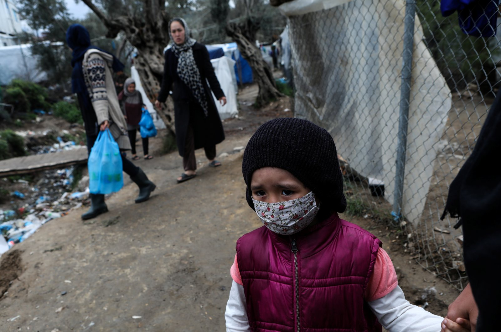 A girl wears a protective face mask at a makeshift camp for refugees and migrants in Lesbos, Greece, Thursday, April 2, 2020. (Reuters Photo)