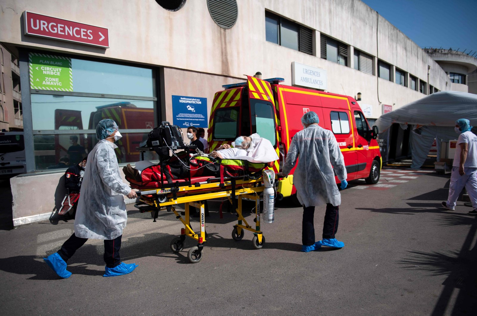 Health workers wearing protective gear ransport a patient on a stretcher toward a tent used as the reception of the emergency services of the Aix Hospital Centre (Centre Hospitalier du Pays d'Aix) in Aix-en-Provence, southern France, on April 3, 2020, on the eighteenth day of a lockdown in France aimed at curbing the spread of the COVID-19 infection caused by the novel coronavirus. (AFP Photo)