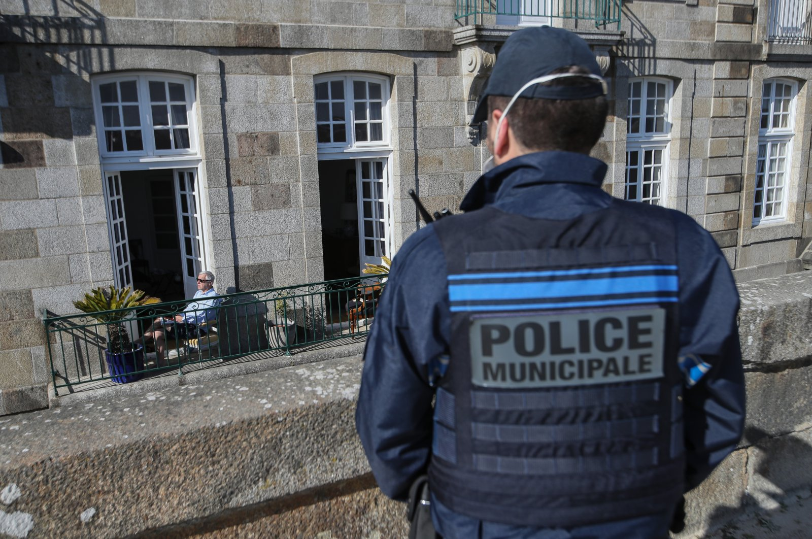 A man reads a book on his sunny terrace's apartment as French police patrol the streets of Saint-Malo, western France, Friday, April 3, 2020. (AP Photo)