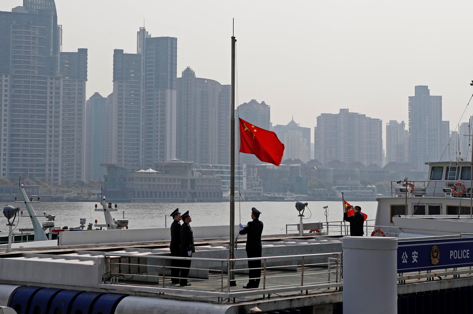 A police officer positions the Chinese national flag at half-mast along Huangpu river in Shanghai, as China holds a national mourning for those who died of the coronavirus disease (COVID-19), on the Qingming tomb-sweeping festival, April 4, 2020. (Reuters Photo)