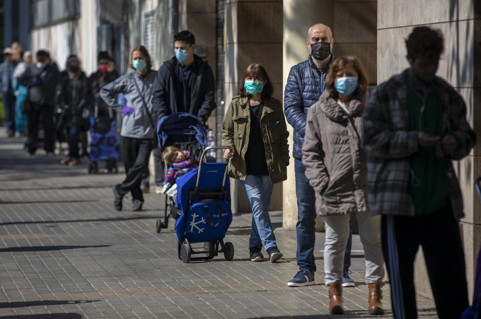 People wearing face masks line up to buy supplies from a shop during the coronavirus outbreak in Barcelona, Spain, Saturday, April 4, 2020. (AP Photo)