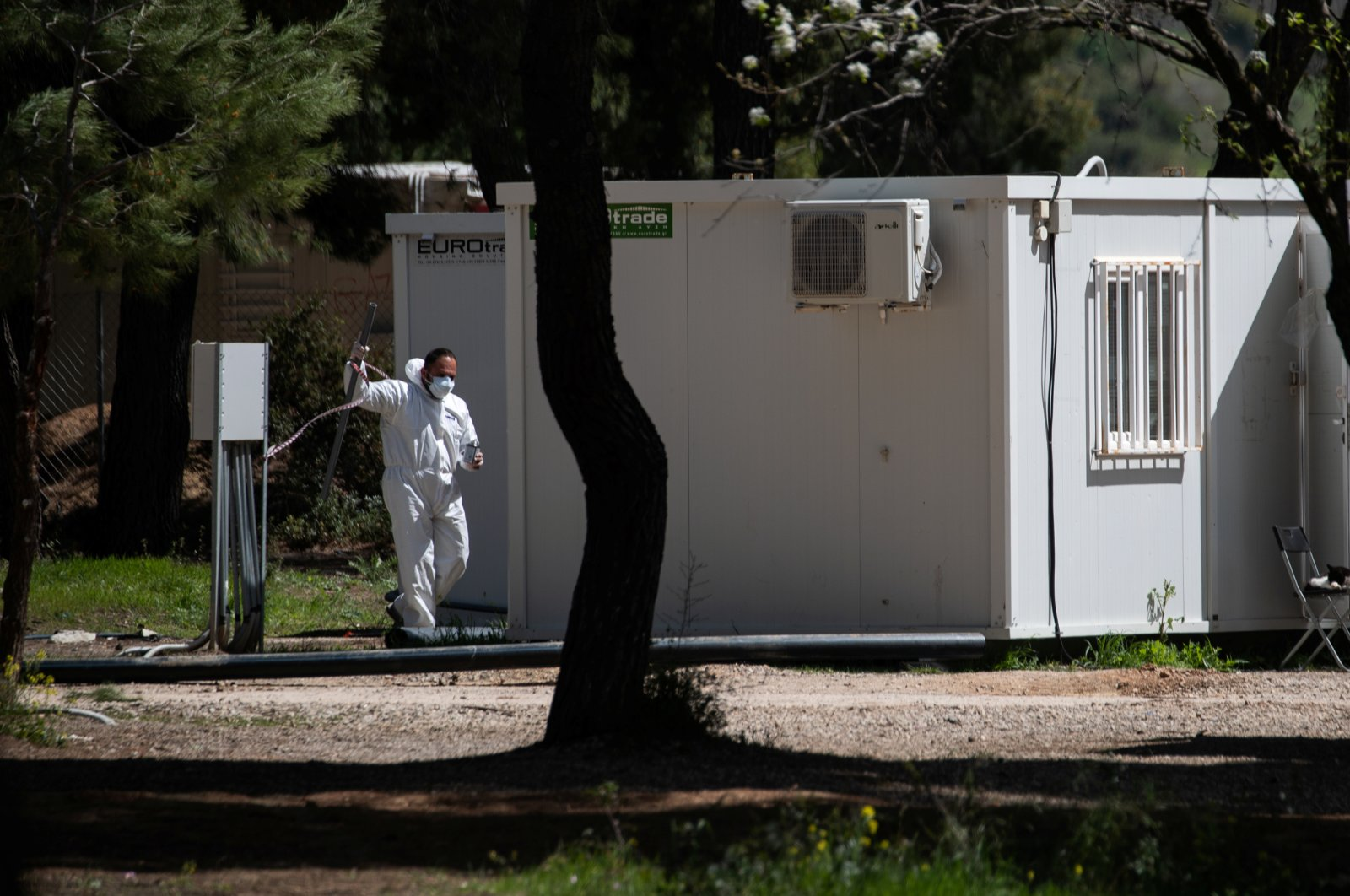 A man wearing a protective suit and a face mask makes his way in the Ritsona migrant camp after authorities found 20 coronavirus cases and placed the camp under quarantine, following the outbreak of coronavirus disease (COVID-19), in Ritsona, Greece, April 2, 2020. (Reuters Photo)